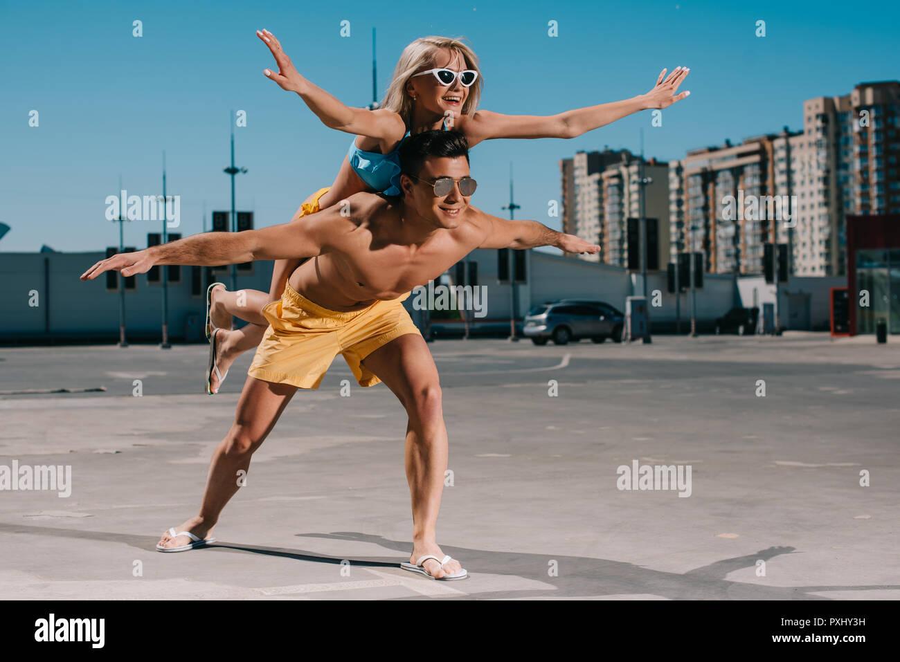 Junge attraktive Frau auf Freund huckepack und Flugzeug Geste auf Parkplatz Stockbild