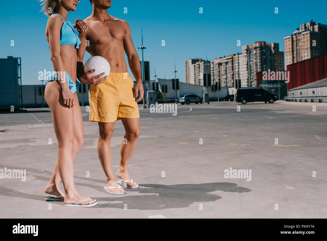 7/8 Schuß des jungen Paares im Strand Kleidung mit Volleyball Ball auf Parkplatz Stockbild