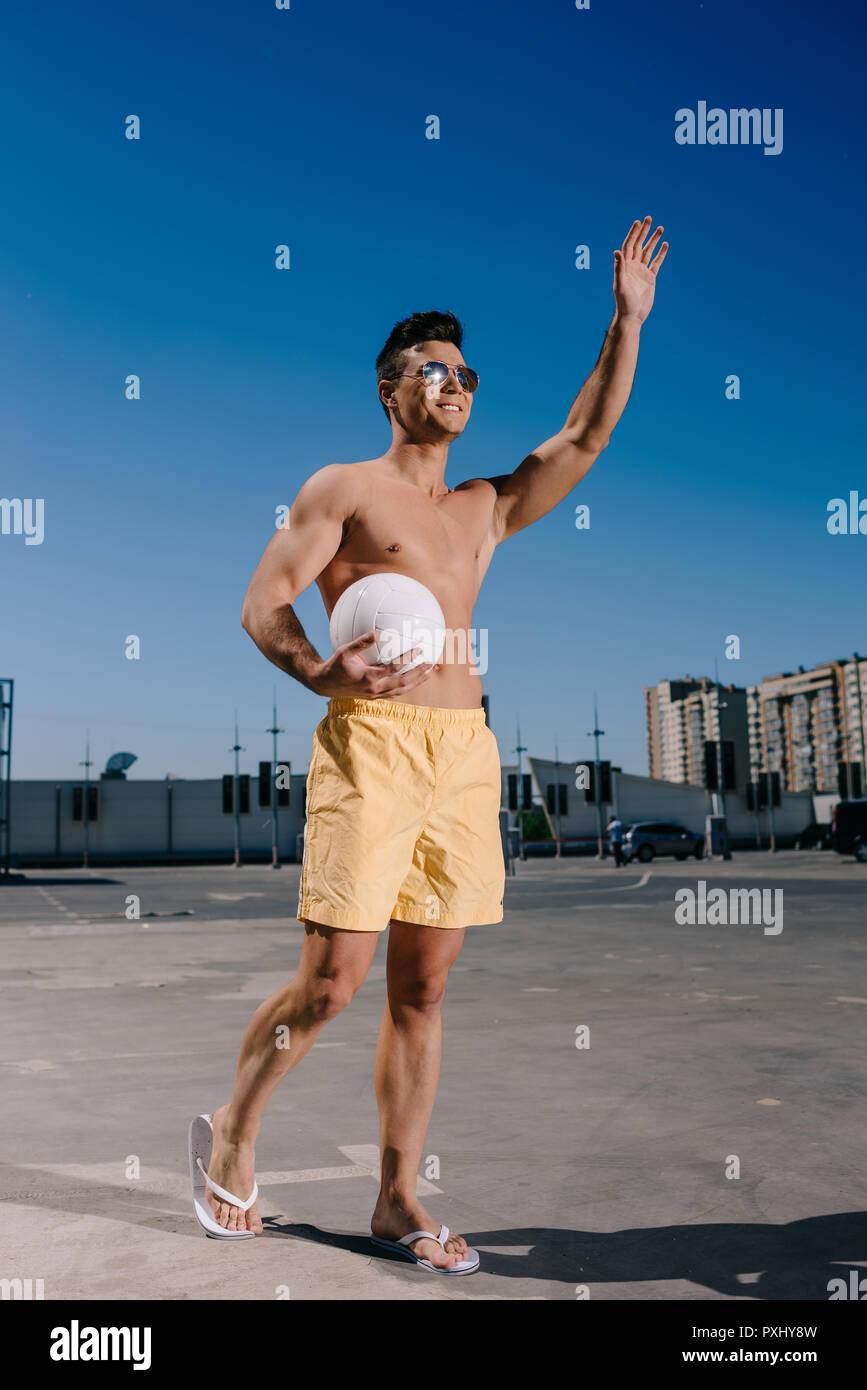 Happy shirtless Mann hält volleyball Ball und winkende Hand auf dem Parkplatz Stockbild