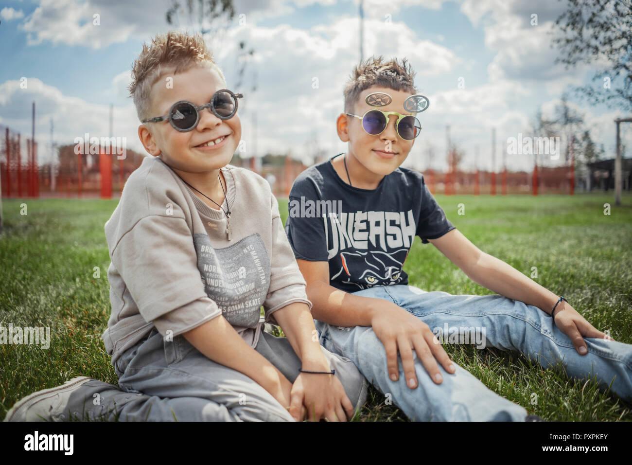 Nahaufnahme von Jungen im Park sitzen auf grünem Gras. Happy Family Konzept. Stockbild