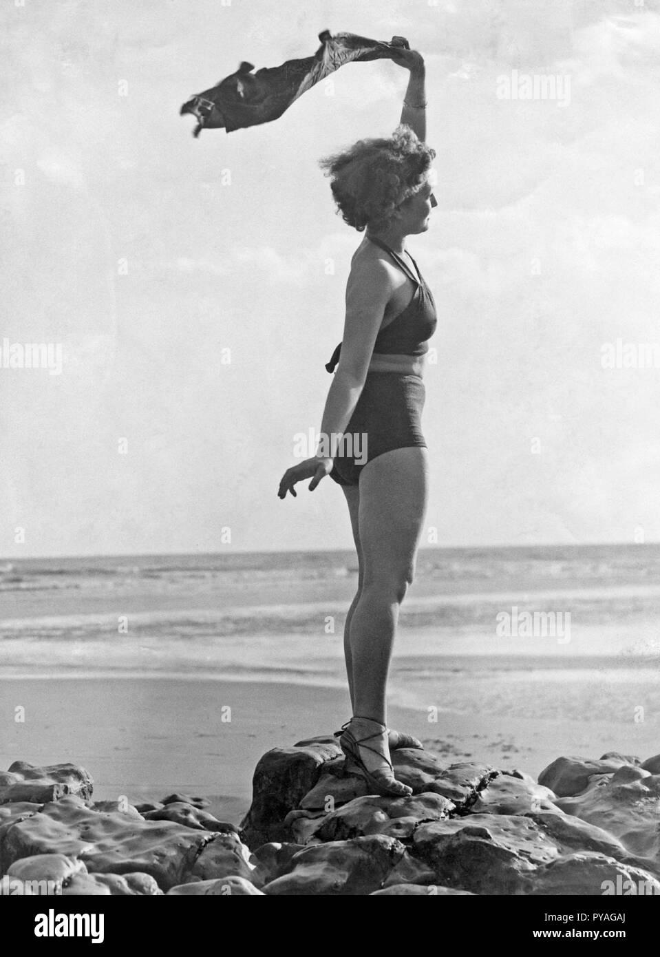 Am Strand, in den 1930er Jahren. Eine junge Frau in einem zweiteiligen Baden Suite, stehend auf dem Strand winkt für jemand. 1930er Jahre Stockbild