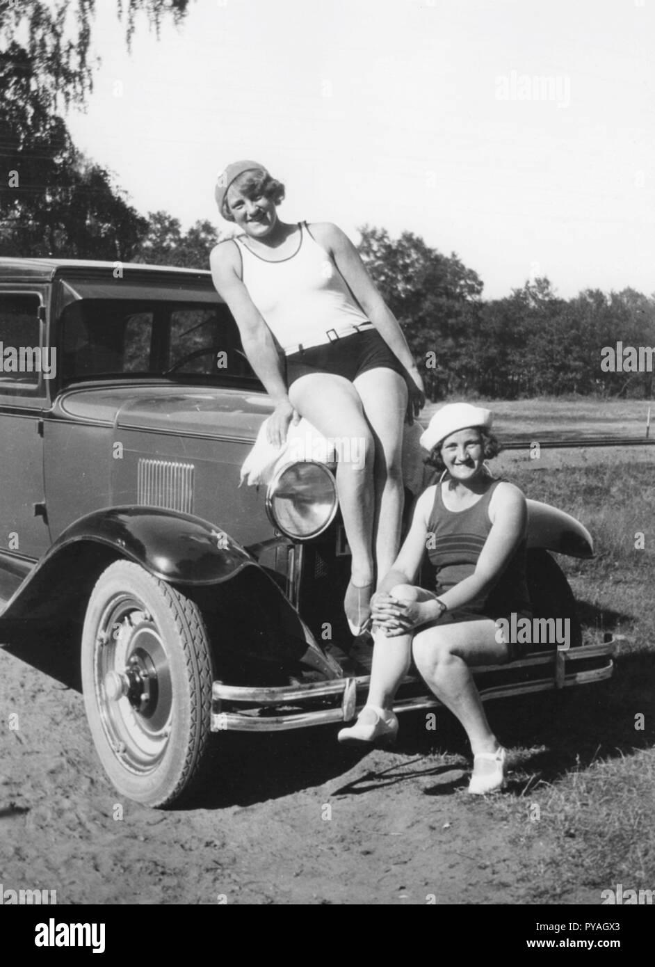 Spaß in den 1930er Jahren. Zwei junge Frauen in Badeanzügen sitzen auf der Motorhaube und vor einem Auto. Schweden 1932 Stockbild