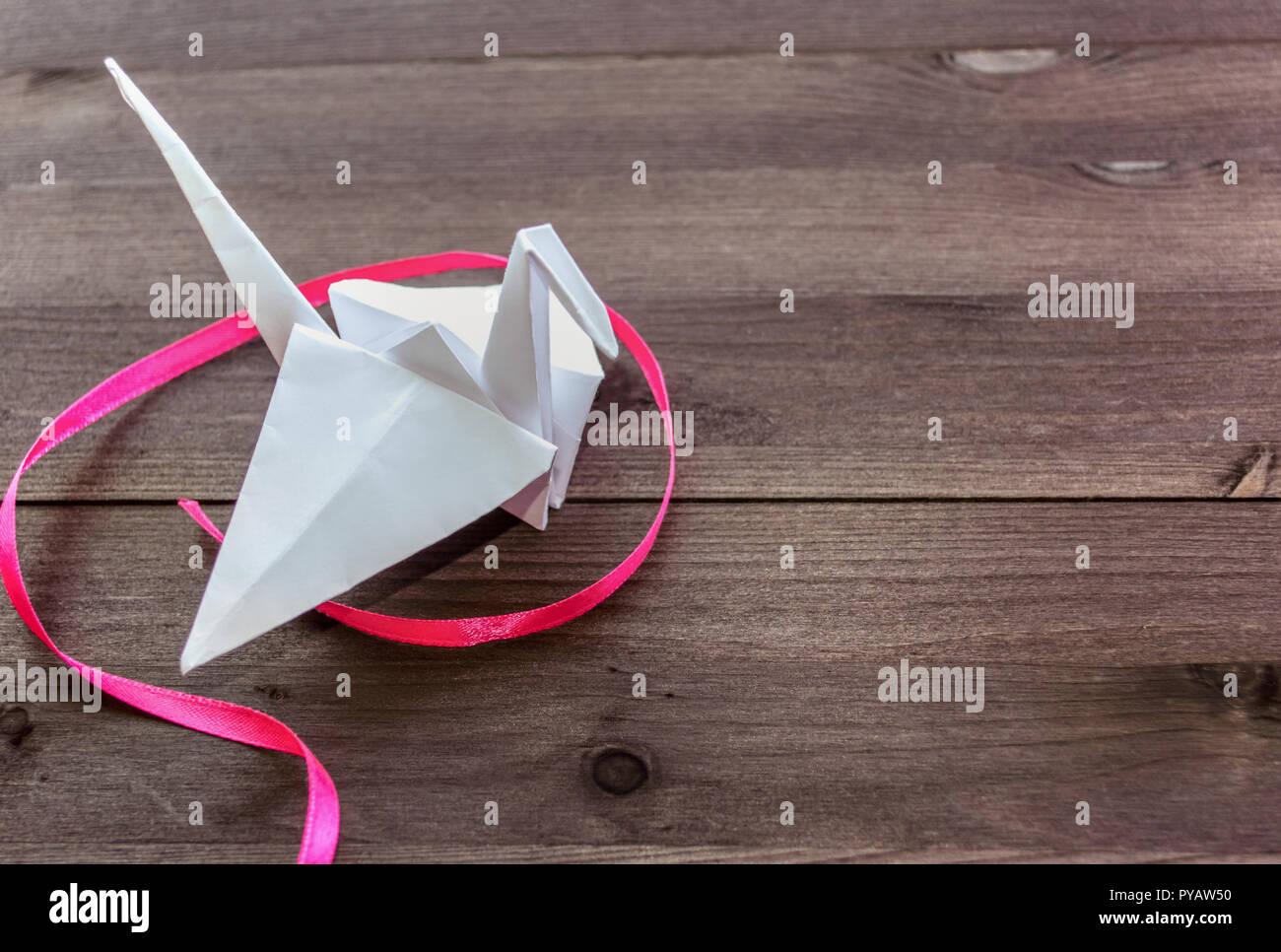 White paper Crane von Pink Ribbon Kurven auf dunklem Hintergrund umgeben Stockbild