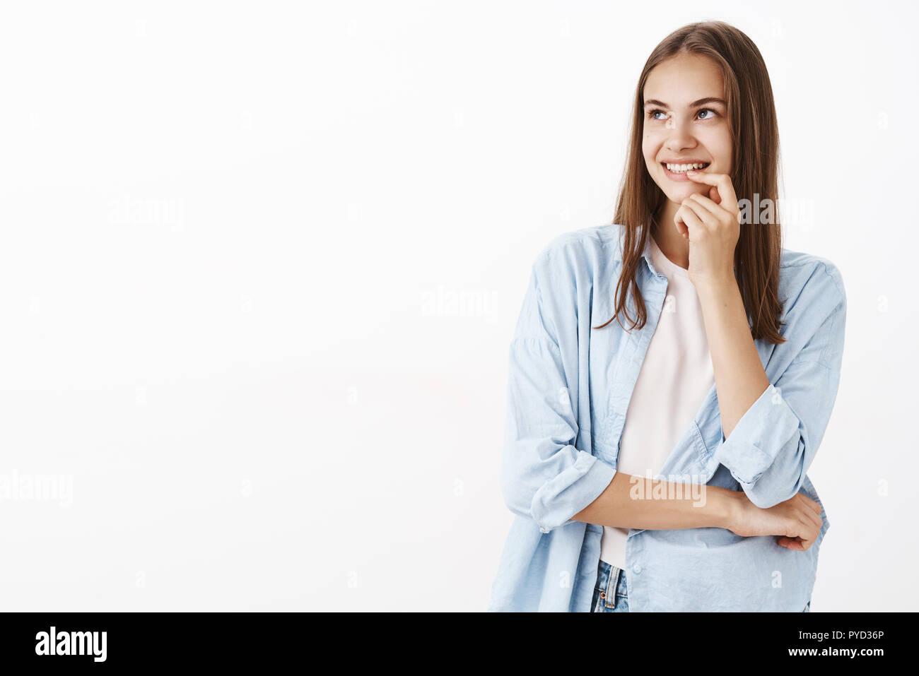 Mädchen eingedenk der erste Kuss mit Freund nostalgisch und flirty Blick auf die obere linke Ecke mit romantischen zufrieden und neugierig Lächeln holding Finger auf Lippe grinsend und Kreuzung Körper mit Arm Stockbild