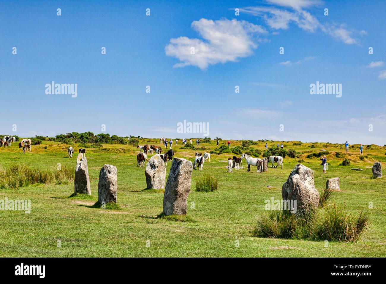 Vom 3. Juli 2018: Bodmin Moor, Cornwall, Großbritannien - The Hurlers Steinkreis in der Nähe von Schergen, das höchstgelegene Dorf in Cornwall, mit wilden Ponys grasen und Menschen t Stockfoto