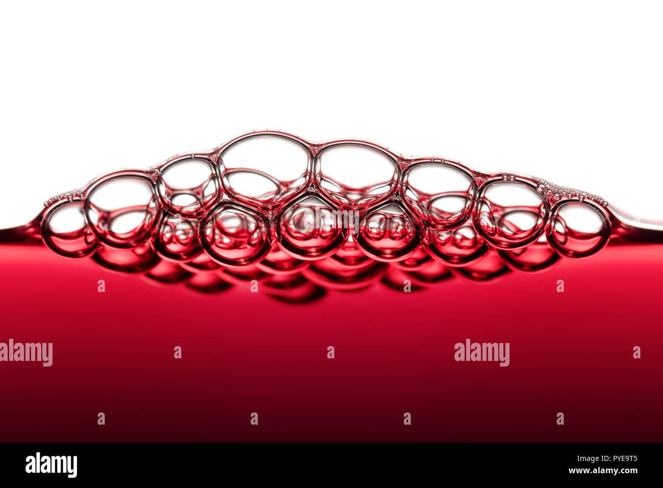 Abstrakte Food Art Muster von Rotwein Blasen fotografiert Close-up vor weißem Hintergrund Stockfoto