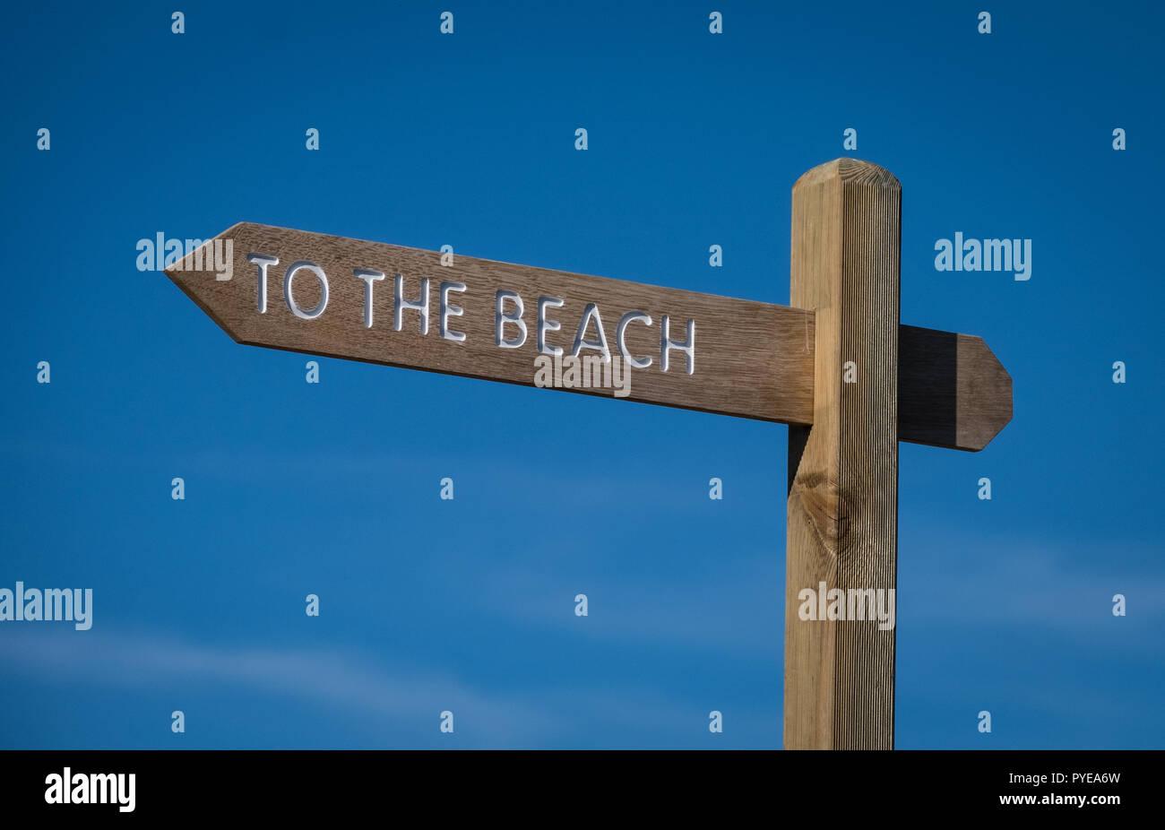 Zum Strand Schild an einem sonnigen Tag vor blauem Himmel Stockbild