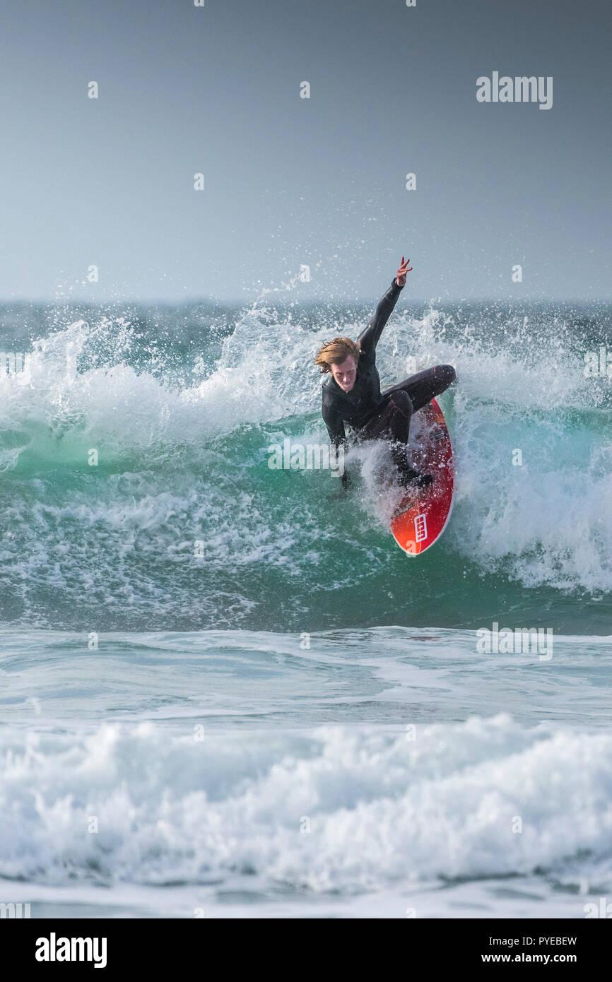 Ein Surfer auf einer Welle in kaltem Wetter Fistral in Newquay in Cornwall. Stockbild