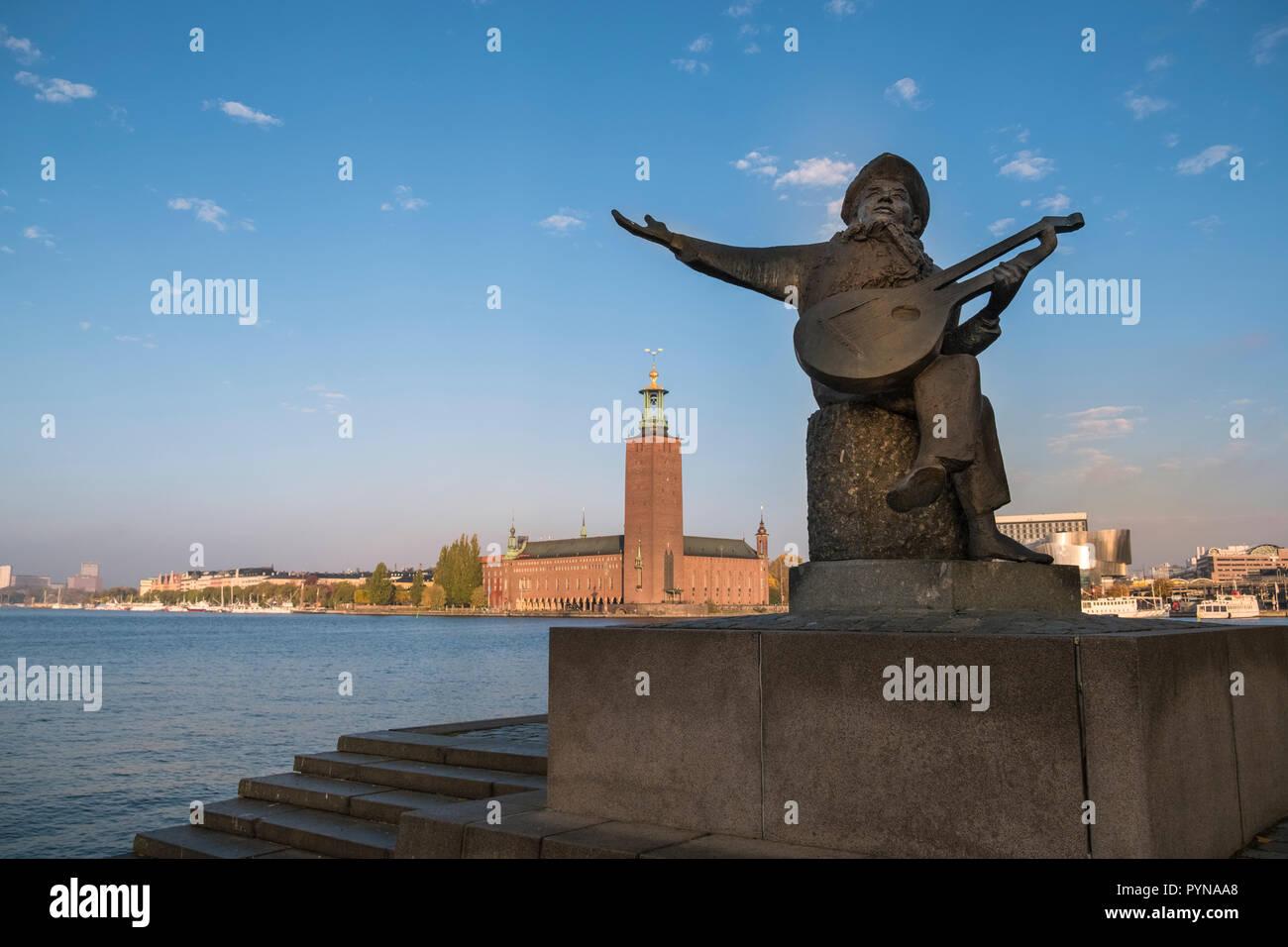 Eine Statue von Evert Taube Wiedergabe der Laute an der Waterfront auf Riddarholmen Insel, mit Rathaus Gebäude im Hintergrund, Stockholm, Schweden. Stockbild