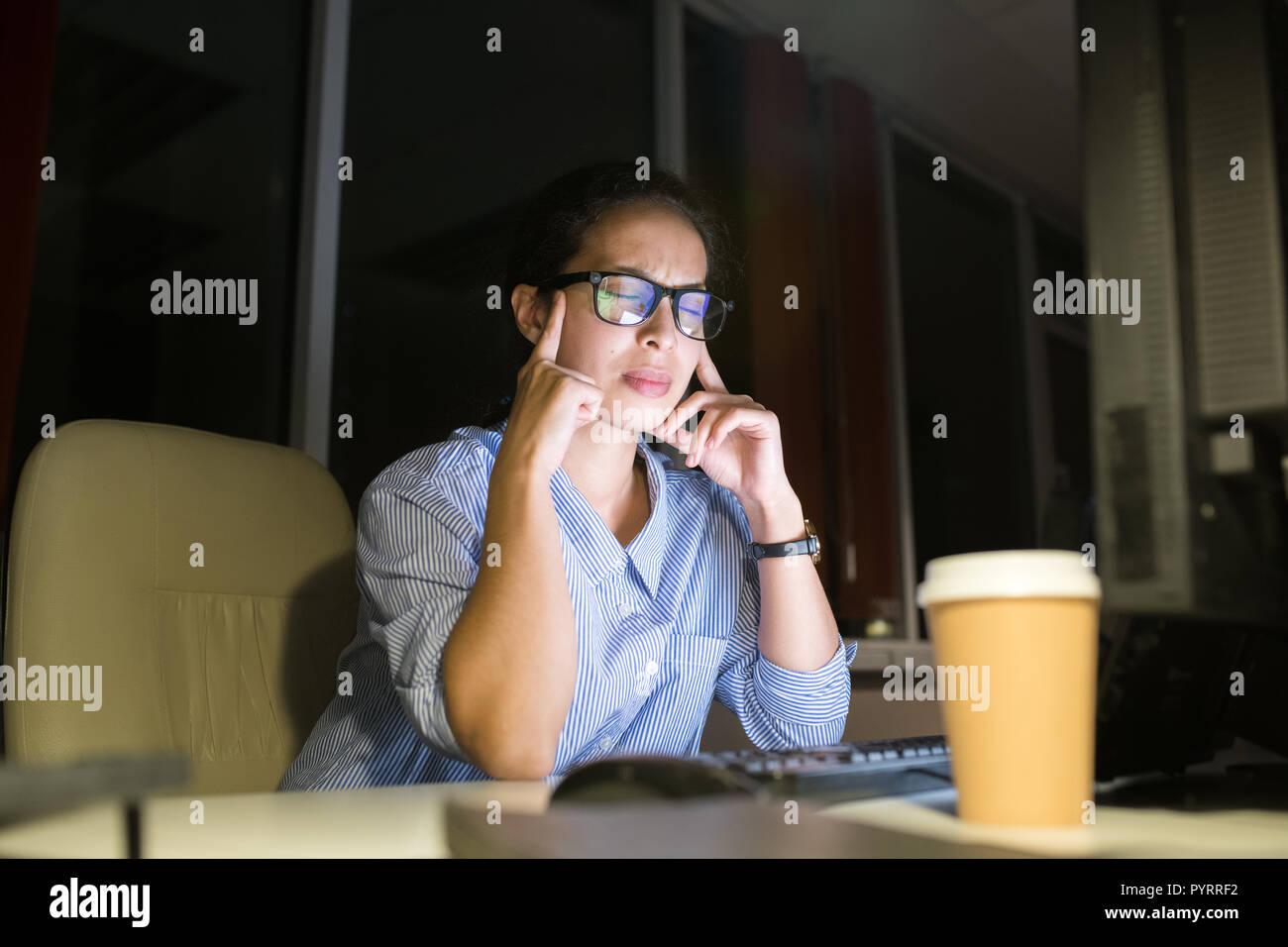 Betonte Frau Arbeiten bei Nacht Stockbild