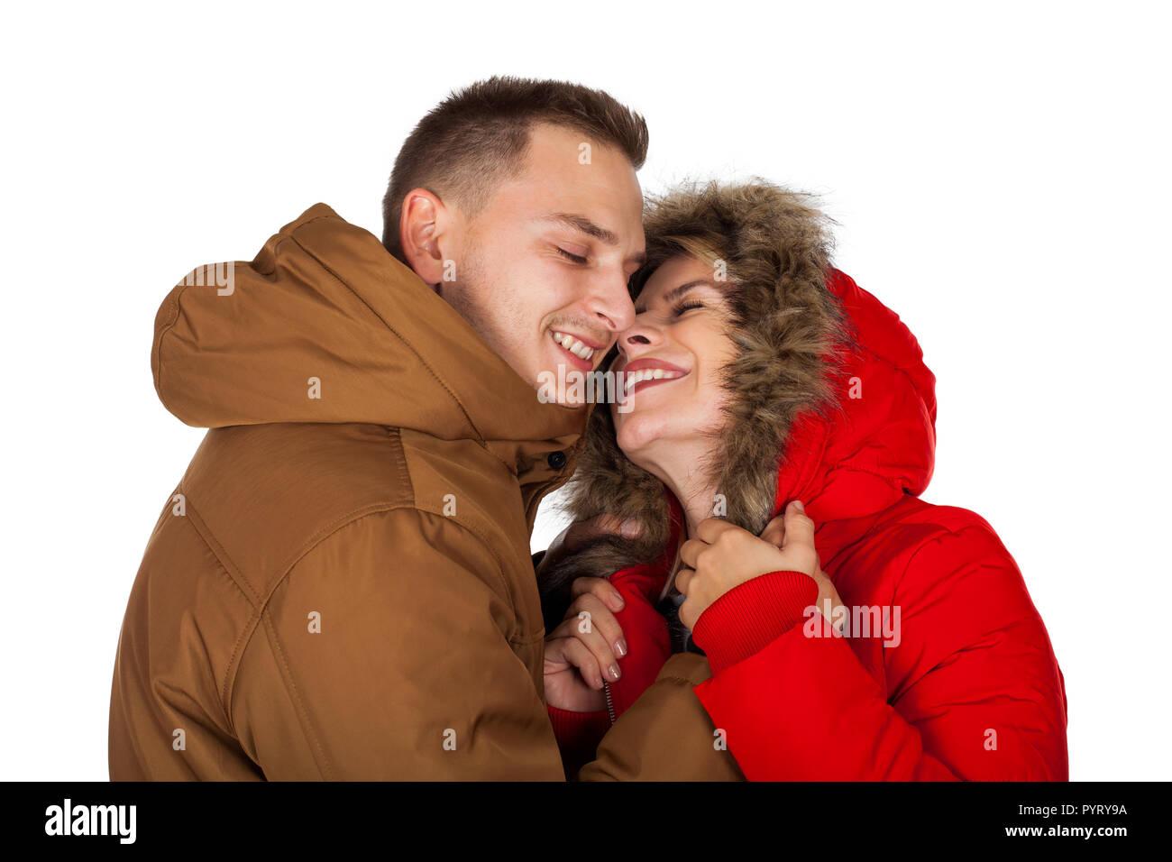 dfec6ca1b162 Junges Paar das Tragen der roten und braunen Winter parka Jacke posiert auf  isolierten Hintergrund -