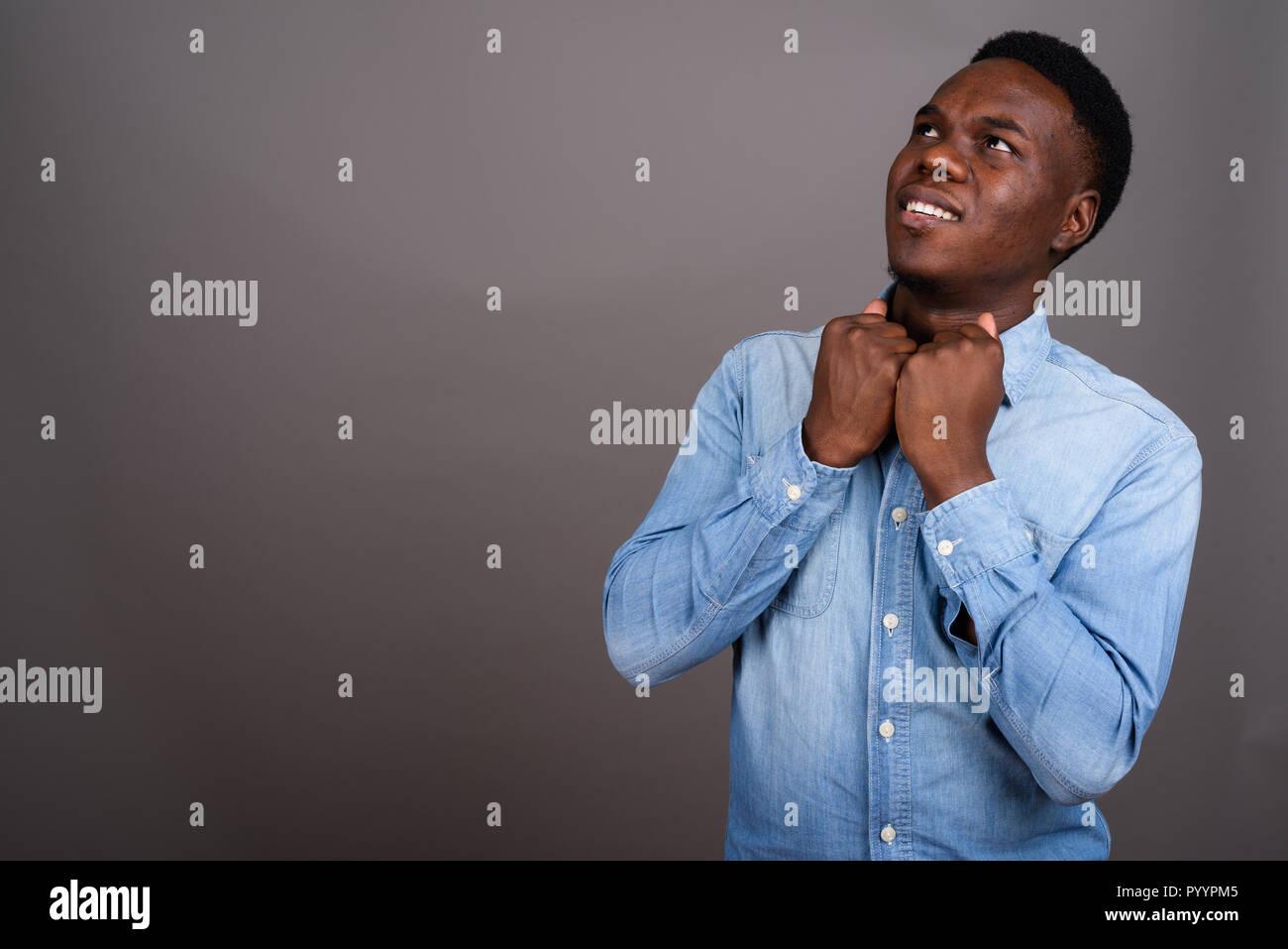 Junge afrikanische Mann tragen Jeanshemd gegen grauer Hintergrund Stockbild