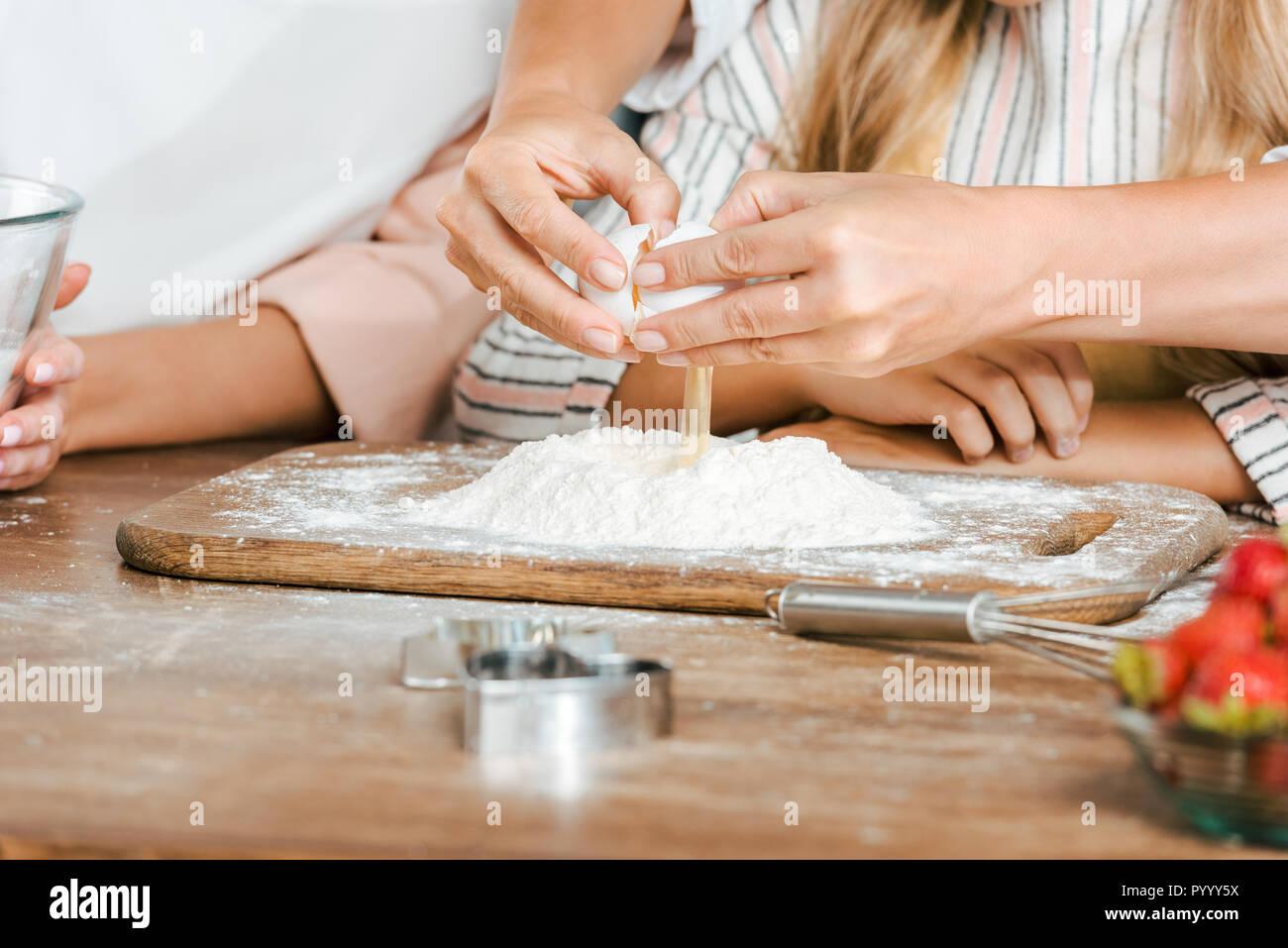 7/8 Schuß von Kind und Frauen Ei in Mehl brechen für Teig auf rustikalen Tisch Stockbild