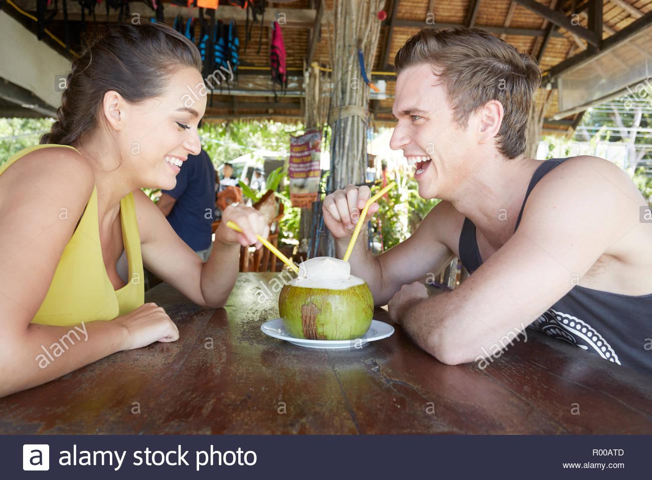 Junges Paar aus Kokosnuss mit Strohhalm trinken Stockbild