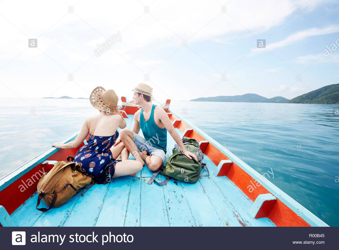 Junges Paar auf Boot mit Rucksäcken Stockbild