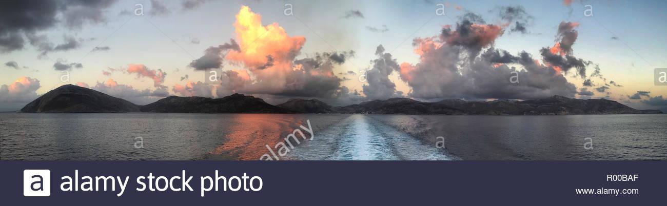 Panorama vom Boot von Wolken über Tilos Insel bei Sonnenuntergang in Griechenland Stockbild