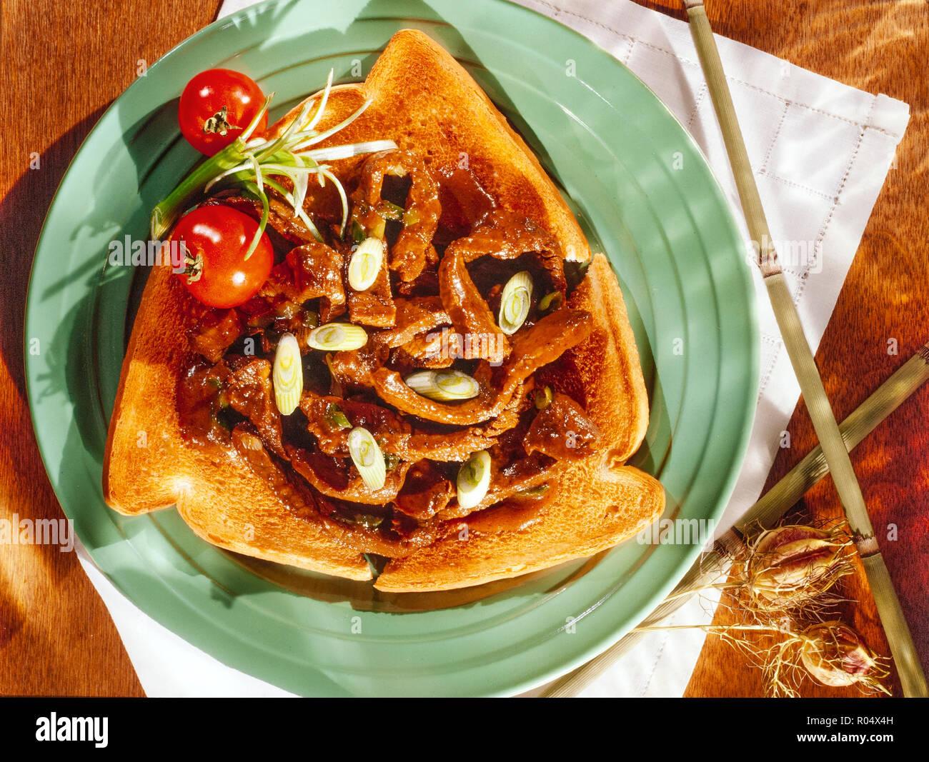 Geschnetzeltes Rindfleisch und Frühlingszwiebeln auf Toast Stockfoto