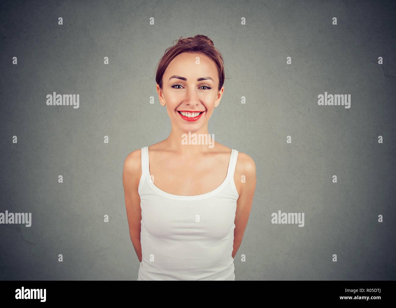 Porträt der charmante junge Frau in weißem tank top Adorably an Kamera lächelnd auf grauem Hintergrund Stockbild