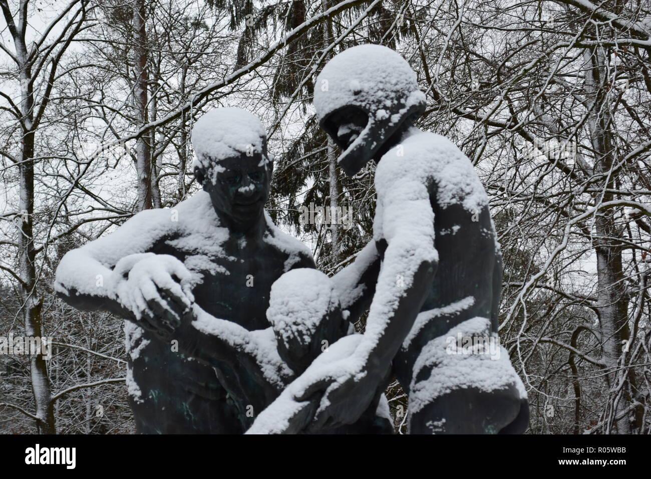 Eine Bronzestatue im Schnee am Soldatenfriedhof in Reimsbach abgedeckt zeigt zwei Männer, die ein tödliches Opfer als Symbol für die Hilflosigkeit der Menschen. Stockbild