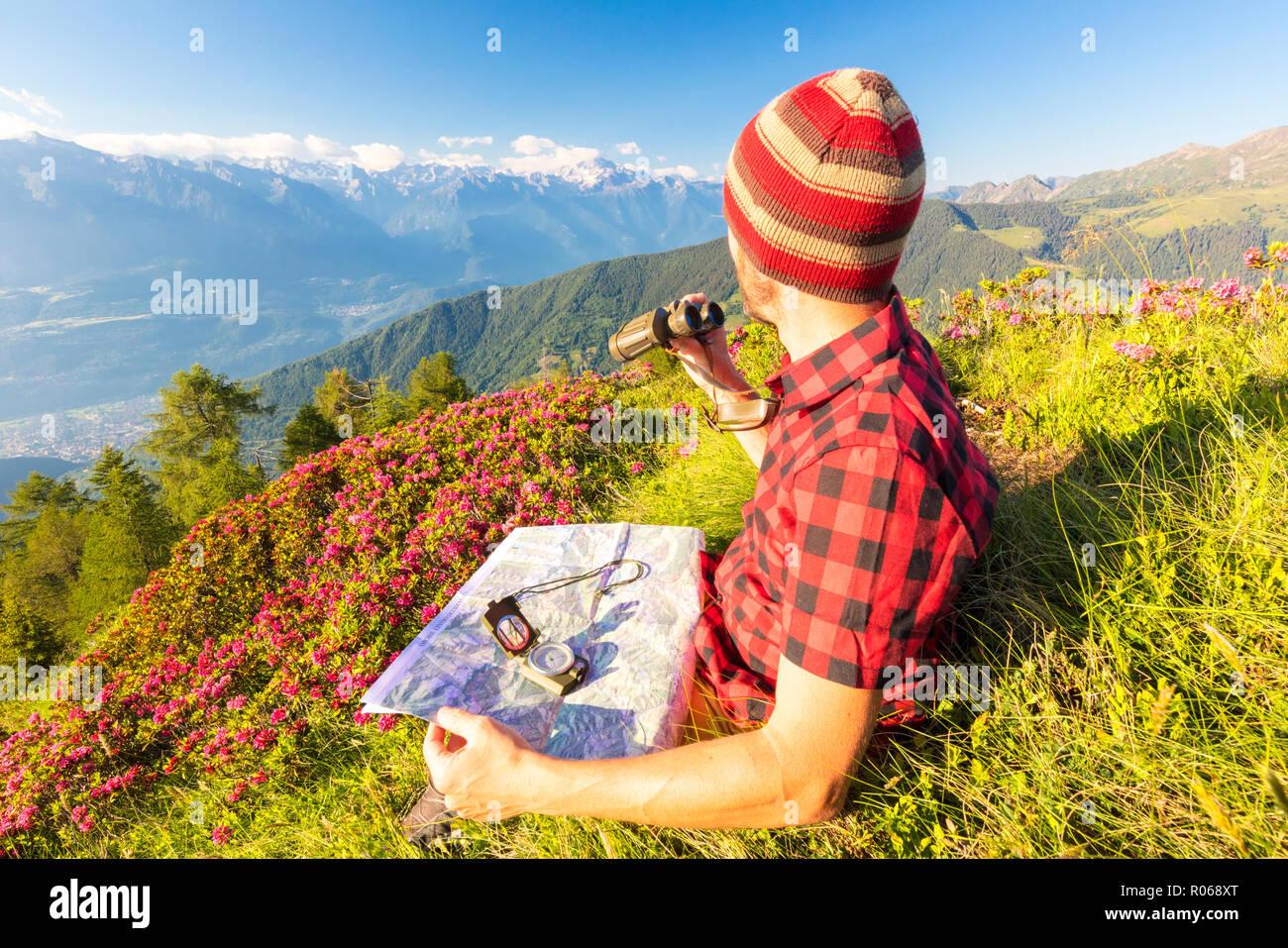 Wanderer mit karte und fernglas schaut in richtung rhätischen