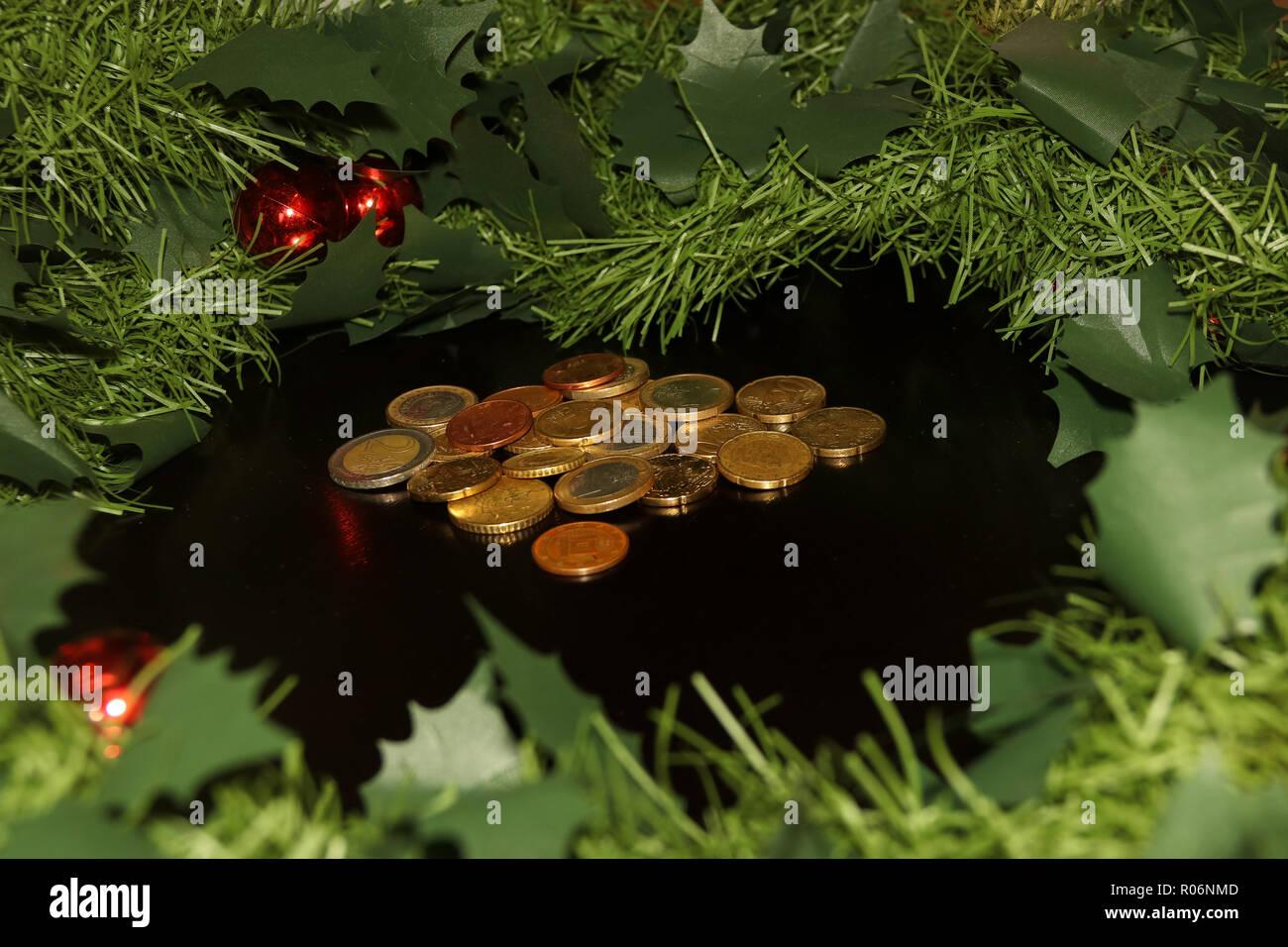 Neues Jahr künstlicher Kranz mit roten Kugeln und Haufen von Euro-münzen in der Mitte der schwarzen Hintergrund Stockfoto