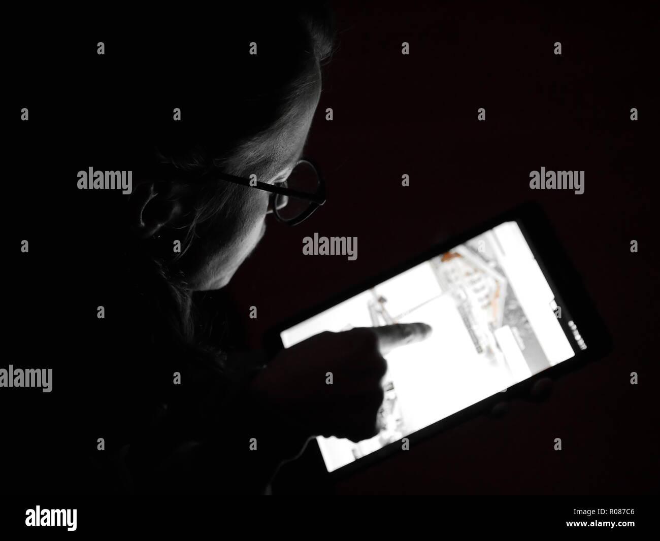 Bild der Frau mit einer Tablette mit einem Finger, wenn es dunkel ist. Stockbild