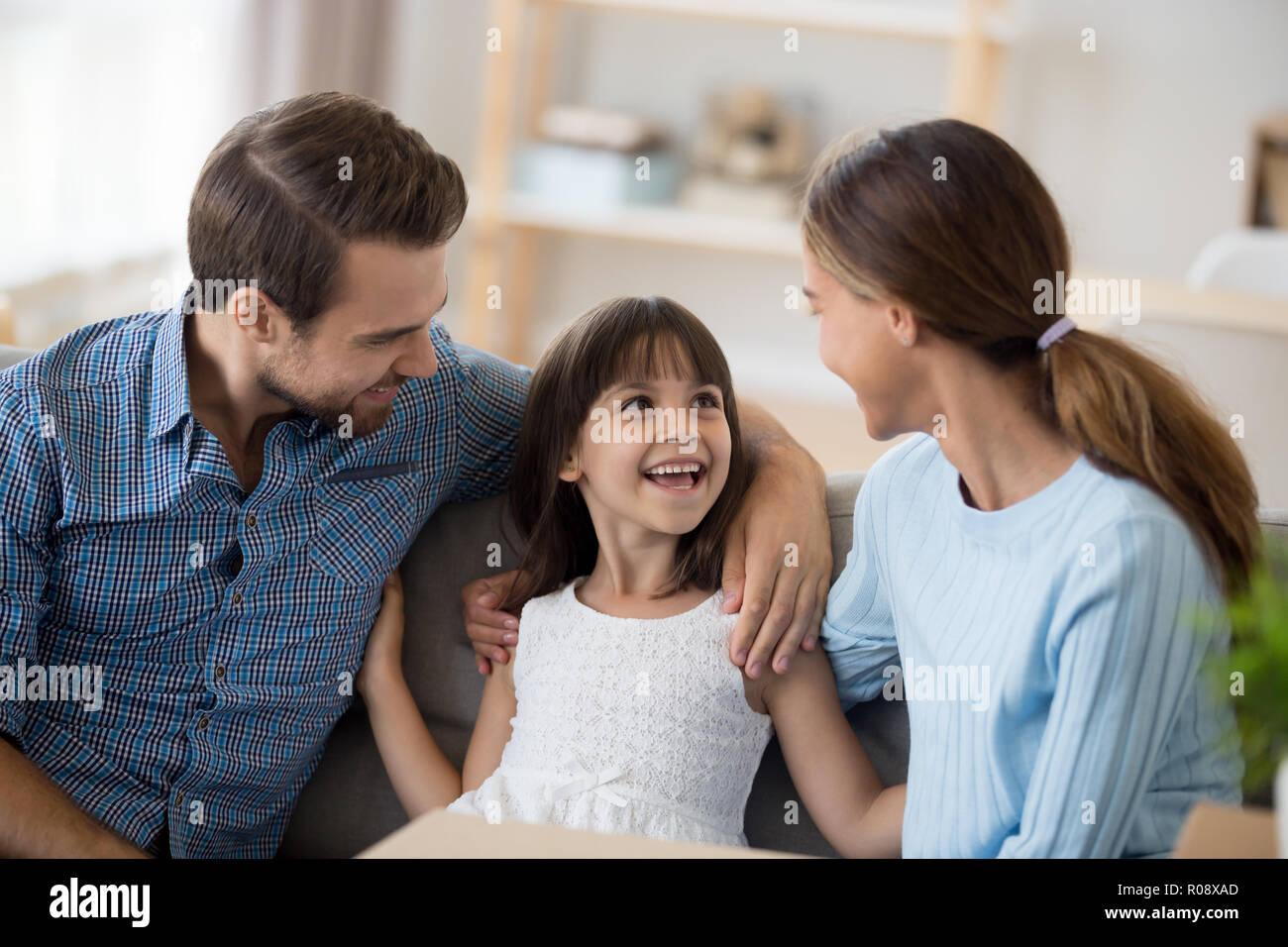 Tochter sitzen gemeinsam mit den Eltern auf der Couch im Wohnzimmer. Stockfoto