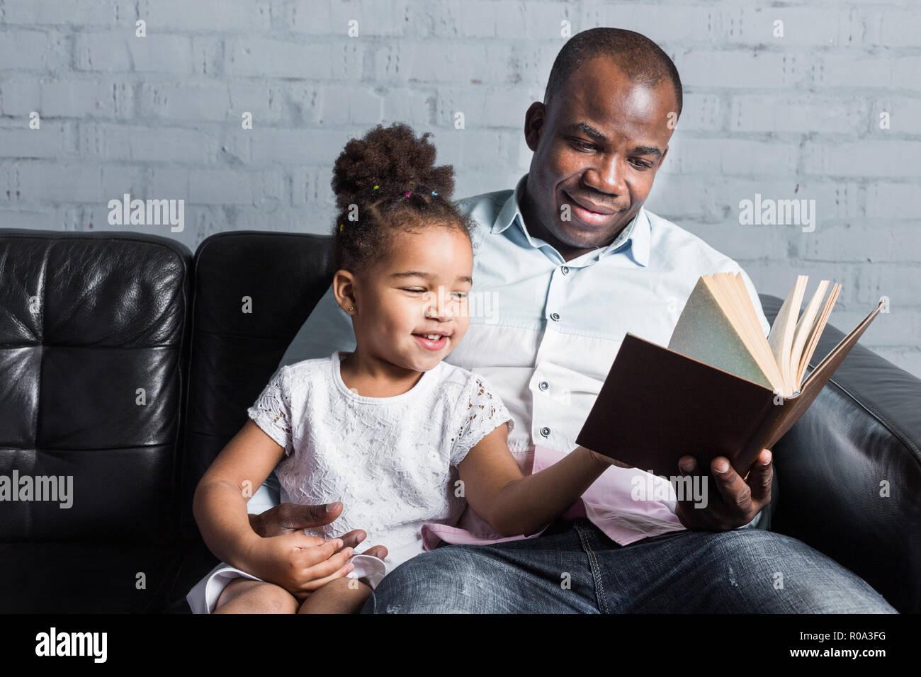 Eltern lesen Sie ein Buch für Kinder sitzen auf der Couch. Happy multiethnischen Familie. Die Werte der Familie Stockfoto
