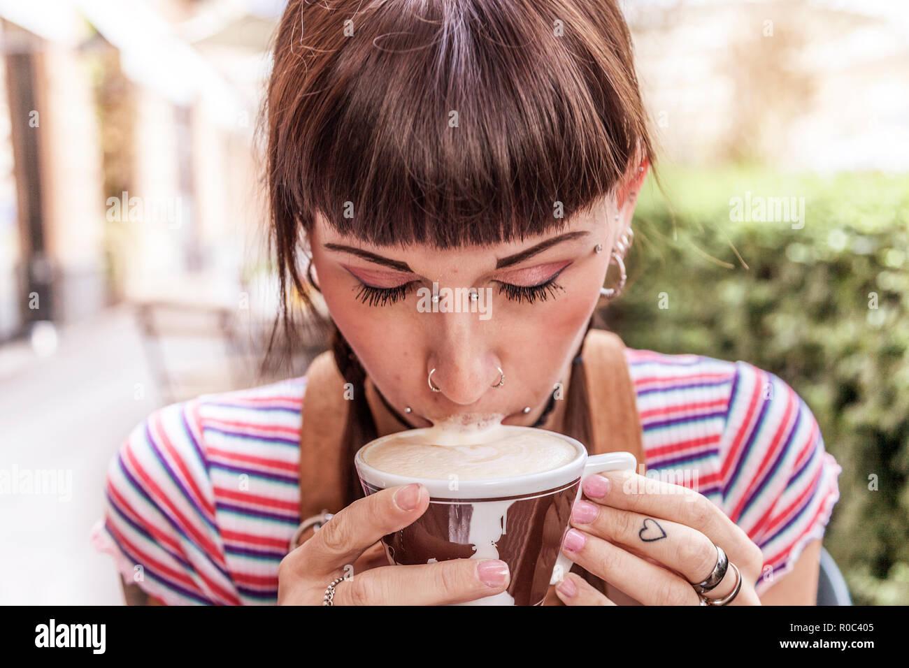 Junge Frau mit blauen Augen ihre Lippen mit Sahne dirty beim Trinken einen italienischen Cappuccino Stockfoto