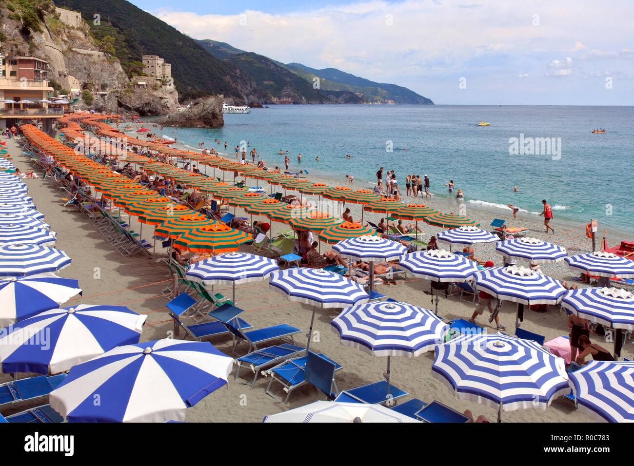 Eine Studie, die in Orange und Grün Sonnenschirme. thie Strand in Monterosso ist die größte in der Cinque Terre. Monterosso al Mare ist eine Gemeinde in t Stockbild
