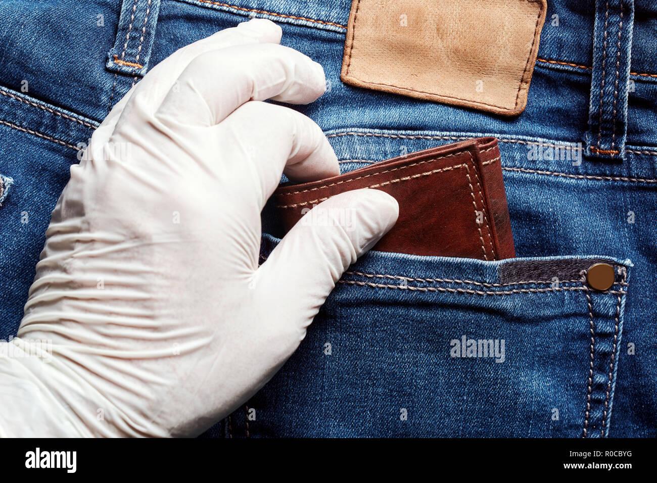 804cf8a261b59 Dieb ein weißes Vinyl Handschuh stiehlt ein Portemonnaie aus der  Gesäßtasche der Jeans. Nahaufnahme von