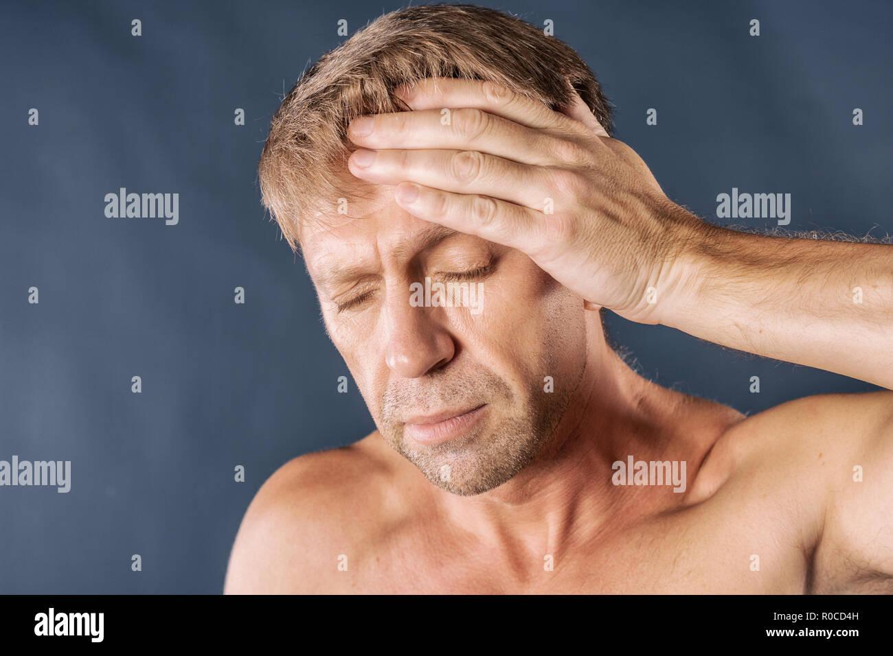 Ein Mann hält seine Hände auf seinen Kopf auf blauem Hintergrund Stockbild