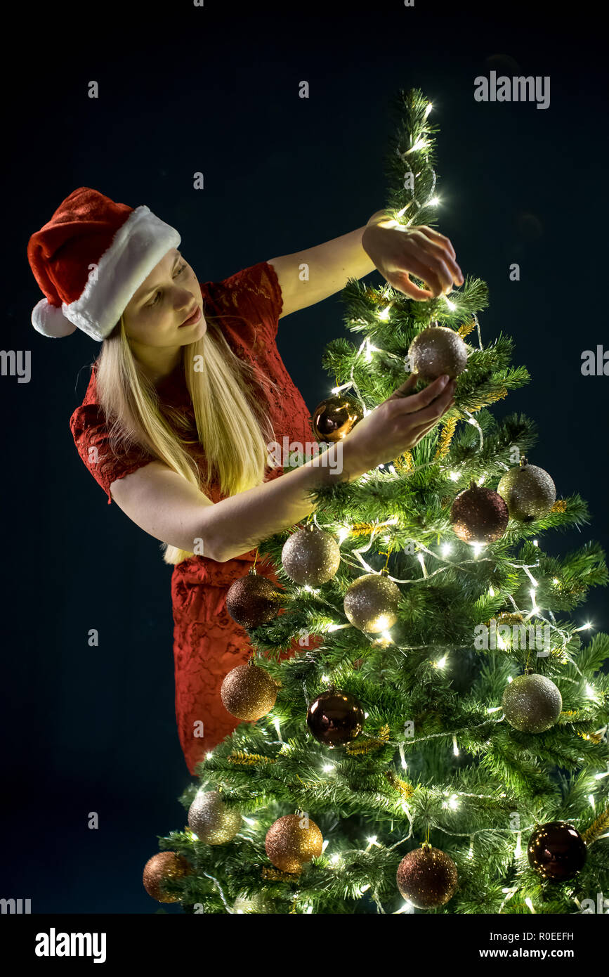 Wer Schmückt Den Weihnachtsbaum.Junge Frau Schmückt Den Weihnachtsbaum Elf Und Mit Dekorationen Aus