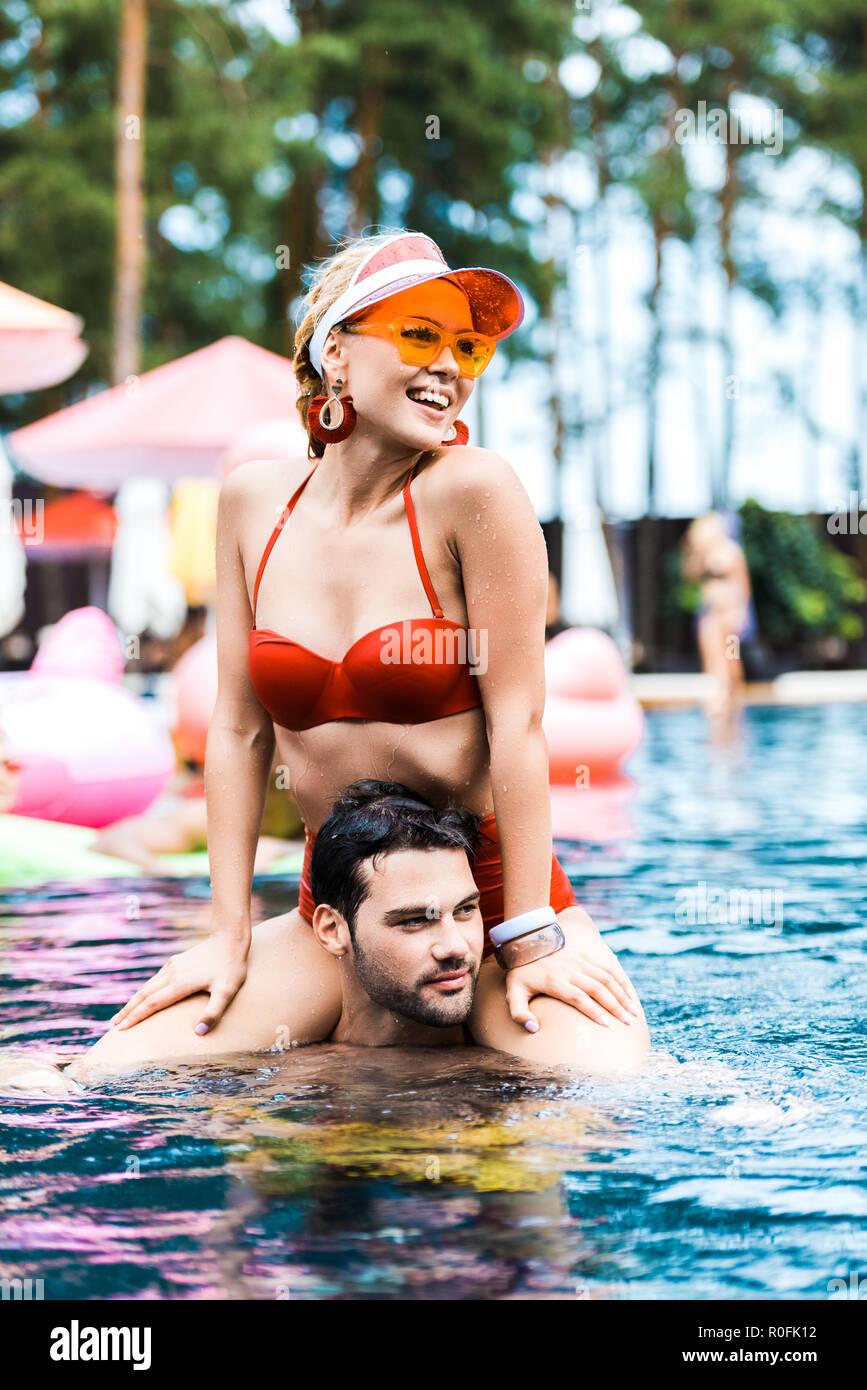 Lächelnde Frau in Rot Badeanzug weg schauen beim Sitzen auf Freunde Schultern im Pool Stockbild