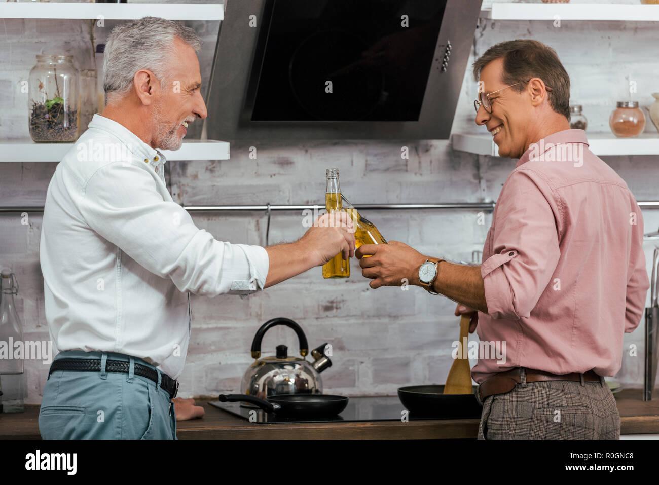 Seitenansicht der lächelnden schönen Männern klirren mit Flaschen Bier, während zu Hause kochen Stockbild