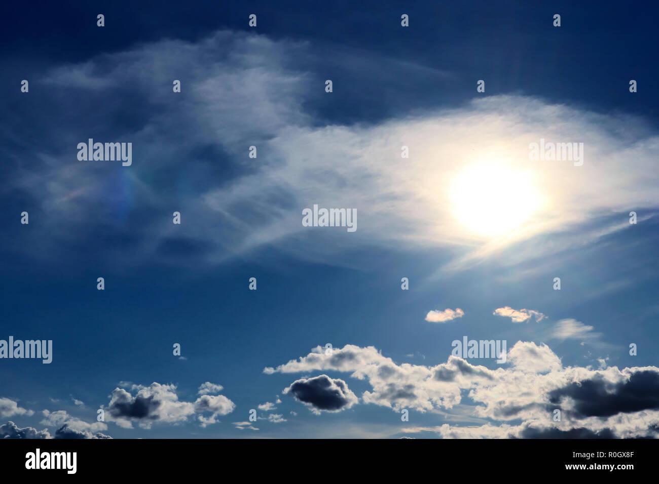 Helle Sonne mit Heiligenschein seine Weise durch die Cirrus Wolken vor blauem Himmel Stockbild