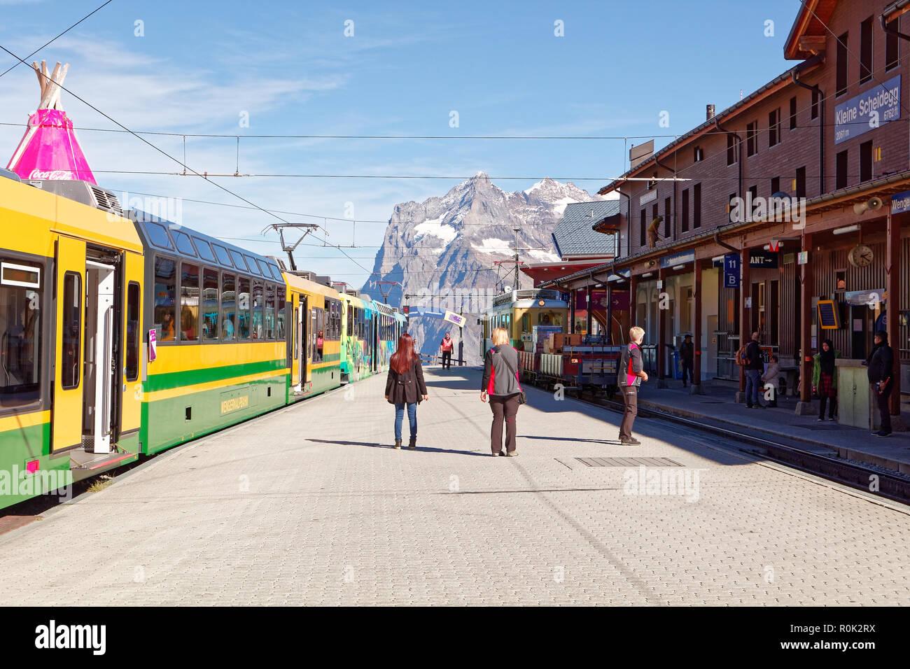 Kleine Scheidegg, Jungfrau Region, Schweiz - Oktober 9, 2018: Besetzt Bahnhof Kleine Scheidegg mit Wetterhorn im Hintergrund und Touristen headi Stockbild
