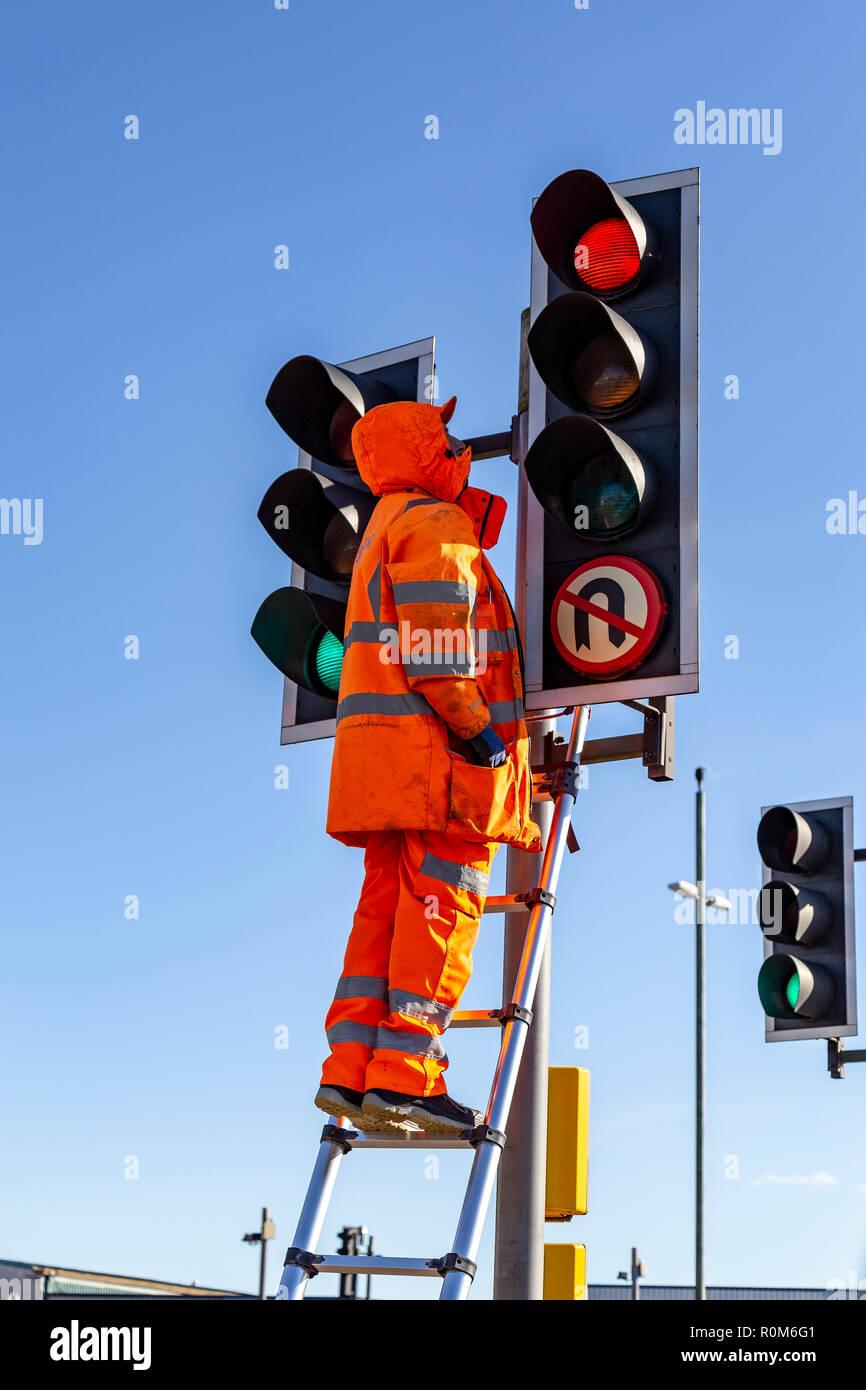 Mann Instandsetzung Ampel automatisch betriebenen bunte Lichter, Verkehr, Kreuzungen, Zebrastreifen, Ampel, Verkehr Stockbild