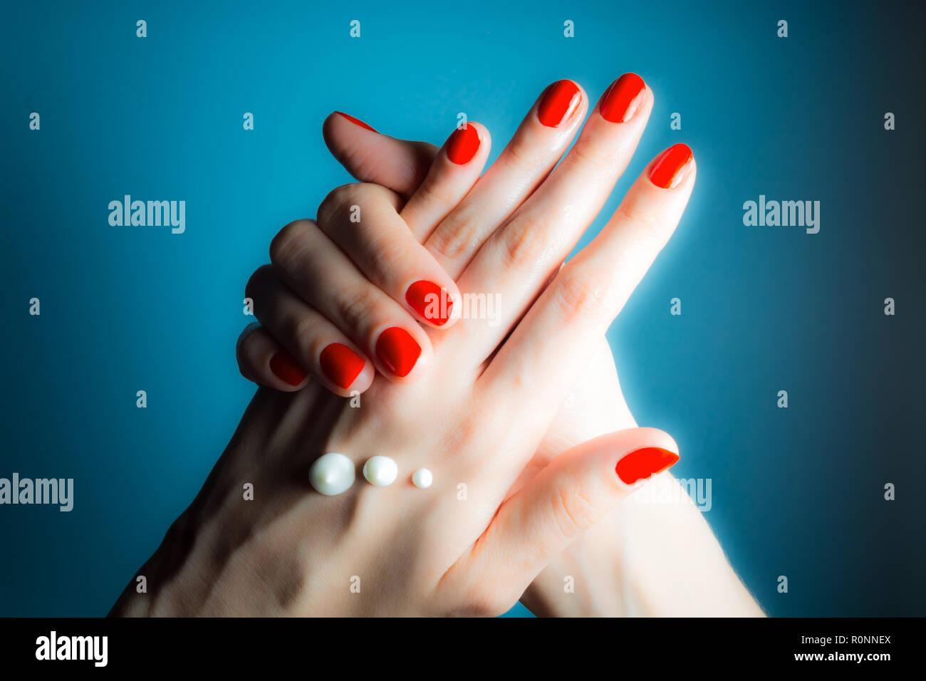 Hände von einem jungen Mädchen mit roten Nägeln und Tropfen Creme close-up auf einem blauen Hintergrund Stockfoto