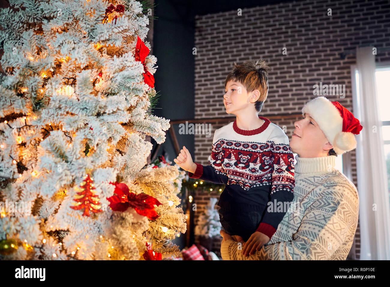 Wer Schmückt Den Weihnachtsbaum.Eine Glückliche Familie Schmückt Den Weihnachtsbaum Zu Hause