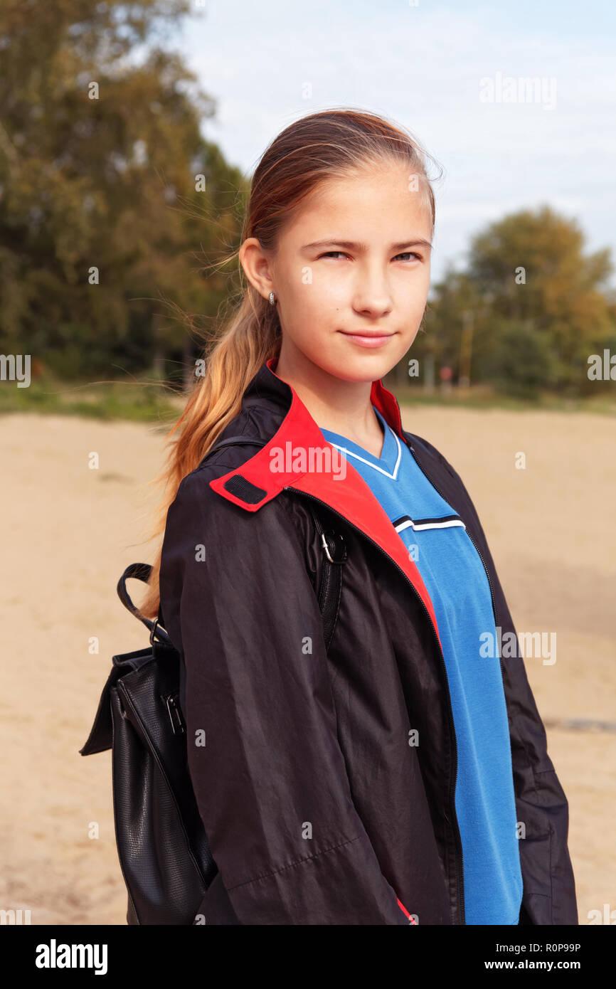 Jugendlicher Mädchen in einem Regenmantel und mit einem Rucksack Wanderungen im Herbst Park Stockbild