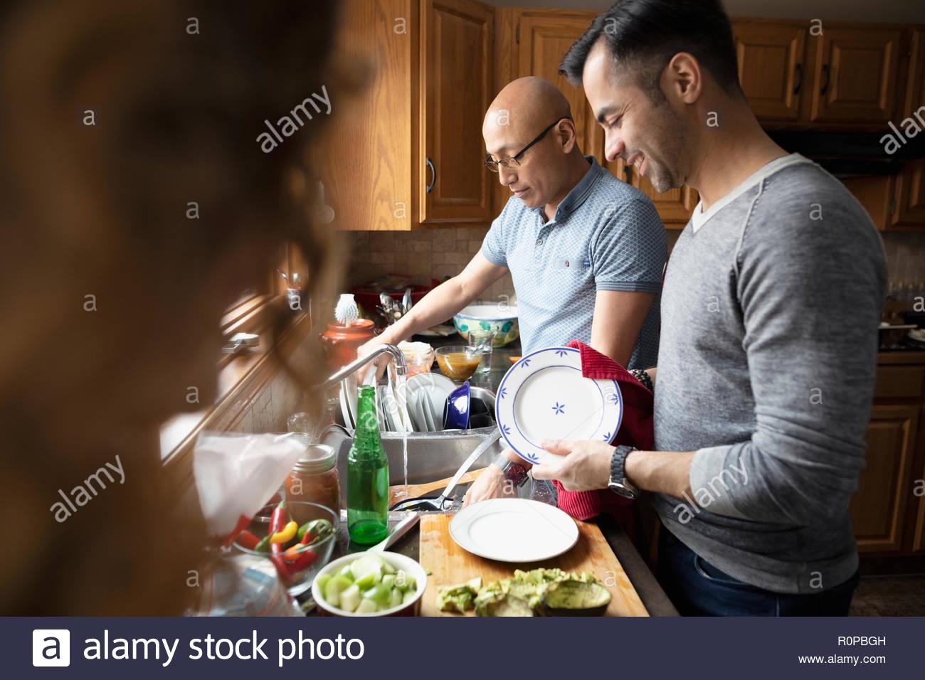 Latinx Männer Gerichte in der Küche Stockbild