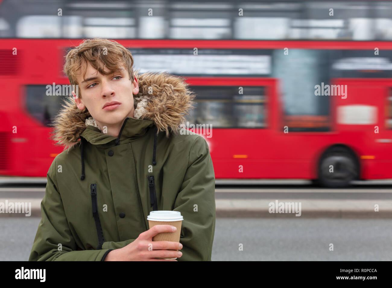 2025f249c037 Nachdenkliches traurig, deprimiert, männliche Junge Erwachsene Teenager  tragen parka Jacke trinken takeout Kaffee in