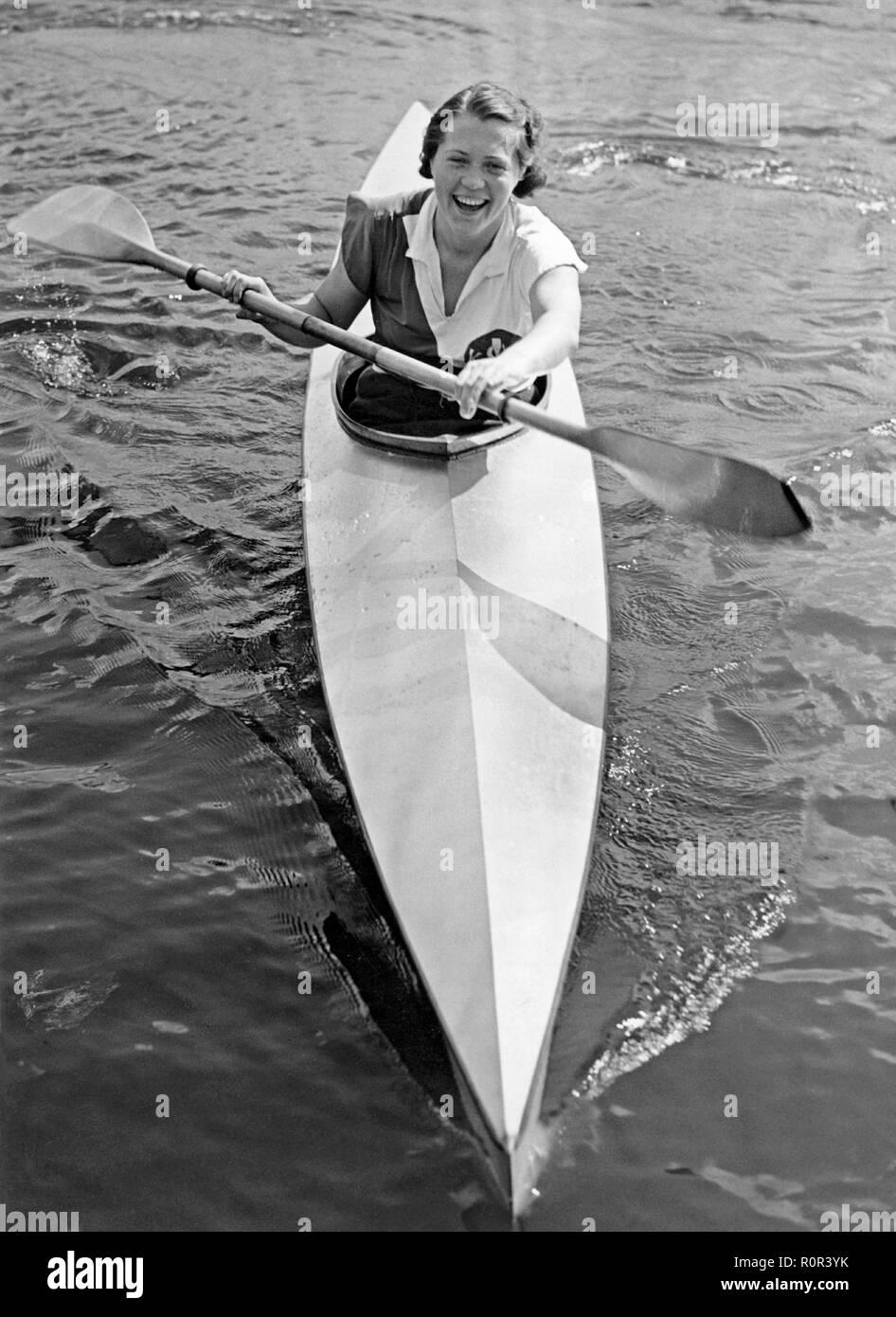 Paddeln Kanu in den 1930er Jahren. Eine junge Frau in einem Kajak, Paddeln auf einem See. Schweden 1937 Stockbild
