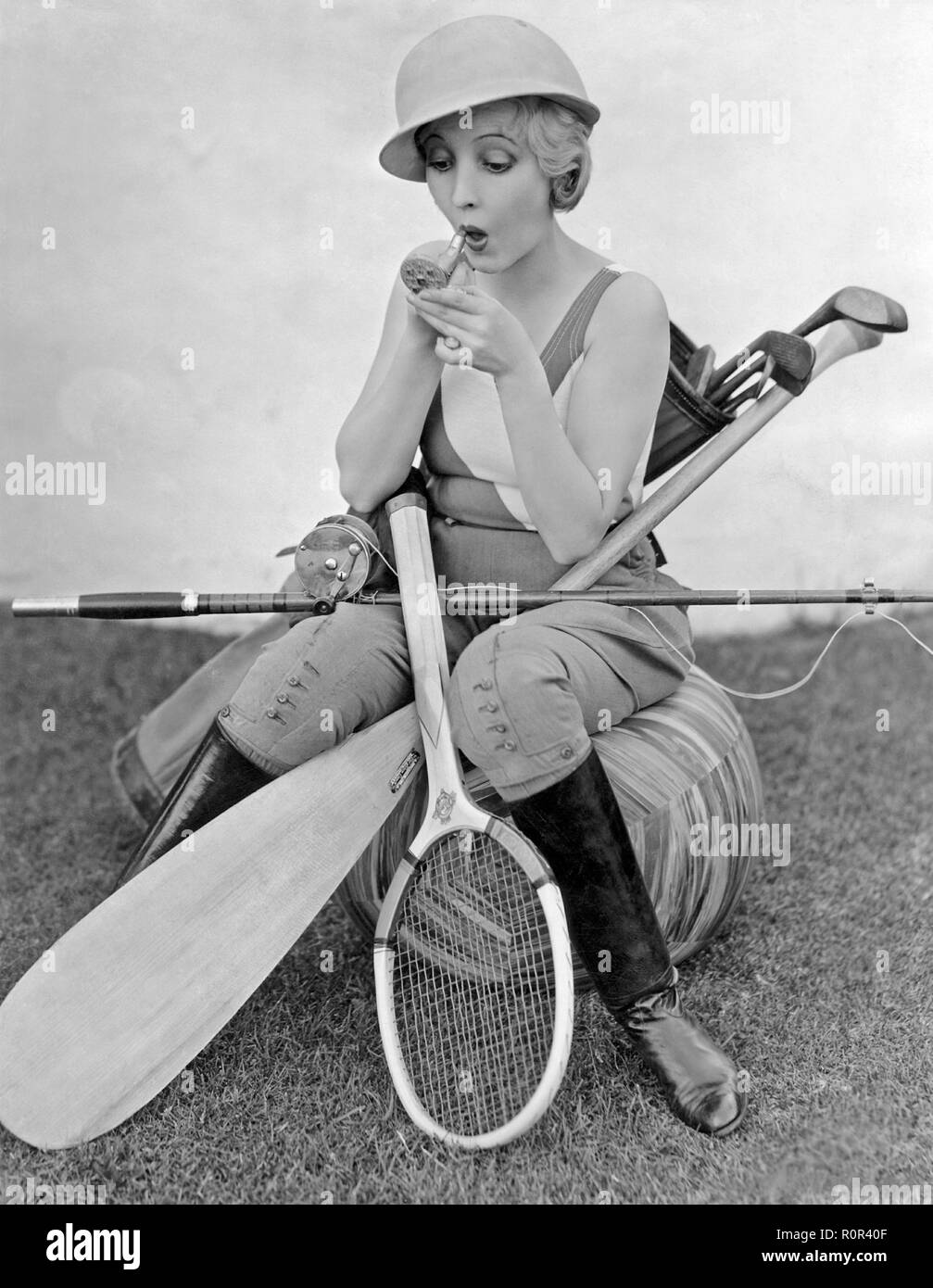 Bessie Love, 1898-1986. Die amerikanische Schauspielerin hier dargestellt mit einem Lippenstift und einen kleinen Taschenspiegel. Sie ist durch verschiedene Arten der Sportausrüstung, Tennisschläger, Angeln, Golf Clubs und ein Kajak Paddel umgeben. 1930er Jahre Stockbild