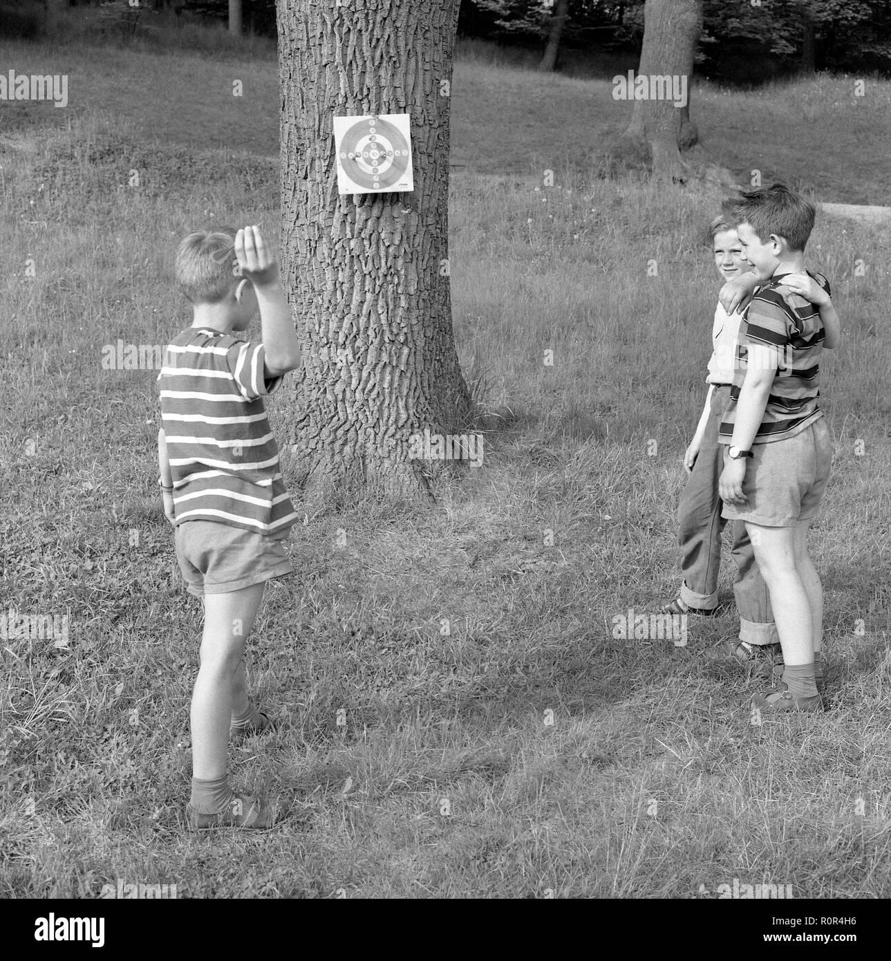 Sommer Aktivität in den 1950er Jahren. Drei Jungen spielen Dart außerhalb. Schweden 1957 Ref 3480 Stockbild