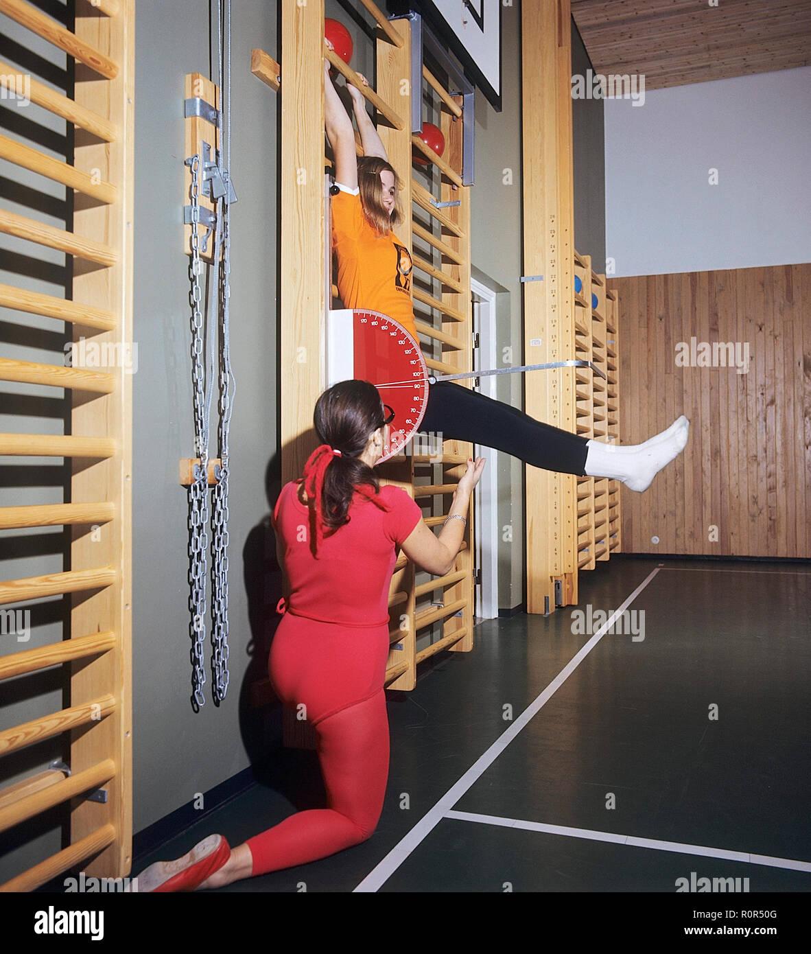 Schule Gymnastik in den 1970er Jahren. Ein Lehrer hilft, ein junges Mädchen während der Gymnastik Klasse. Sie misst den Winkel der Beine mit einer Skala. Schweden 1970 s Stockbild