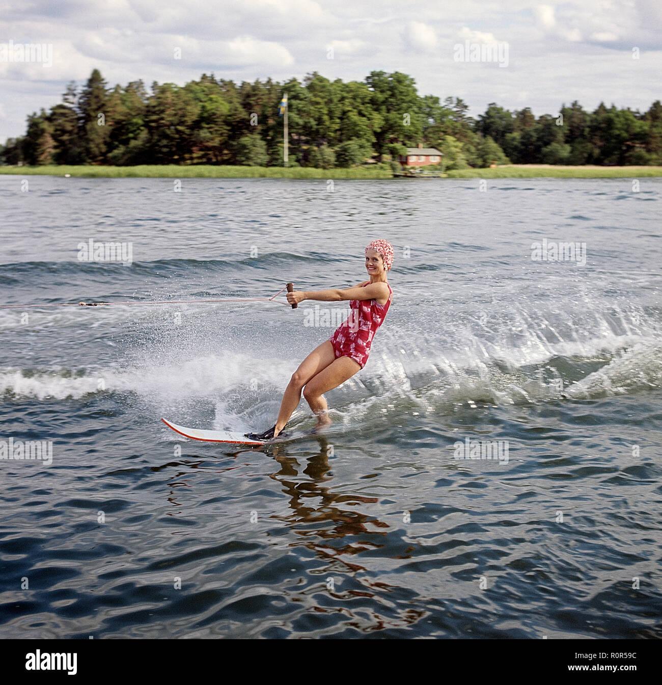 Wasserski in den 1960er Jahren. Eine junge Frau in einem gemusterten Badeanzug übergibt die Fotografen auf ihre Wasserski. Sie hat eine typische Badekappe auf. Schweden 1946 Foto Kristoffersson ref CV 12-7 Stockbild