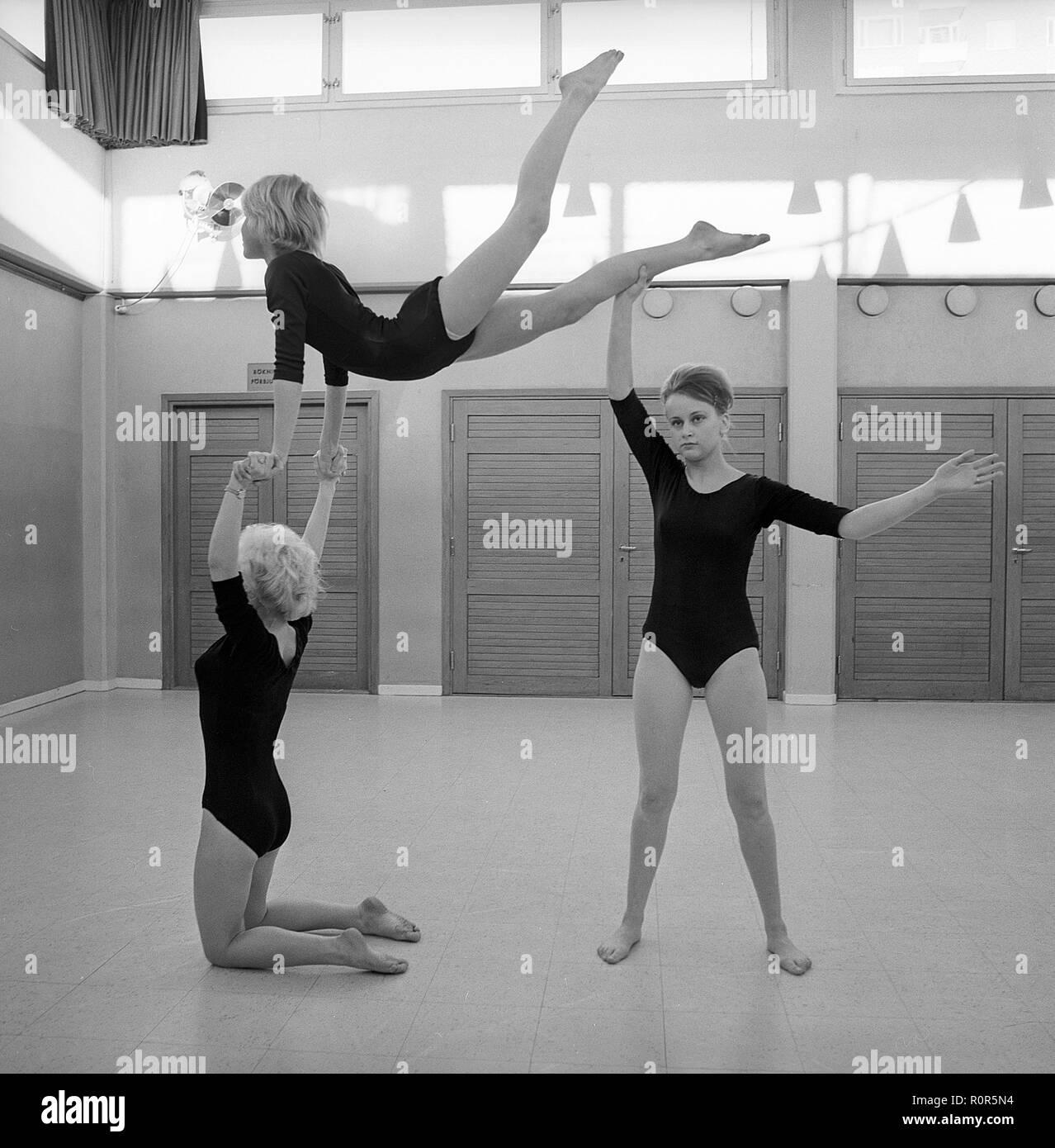 Gymnastik in den 1960er Jahren. Drei Mädchen im Teenageralter praktizieren Gymnastik zusammen in einem Gymnasium Halle. Schweden 1962 Stockbild