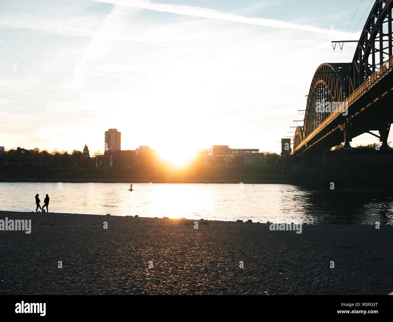 Brücke über den Rhein in Köln bei Sonnenuntergang mit zwei Silhouetten der Frau sprechen Stockfoto
